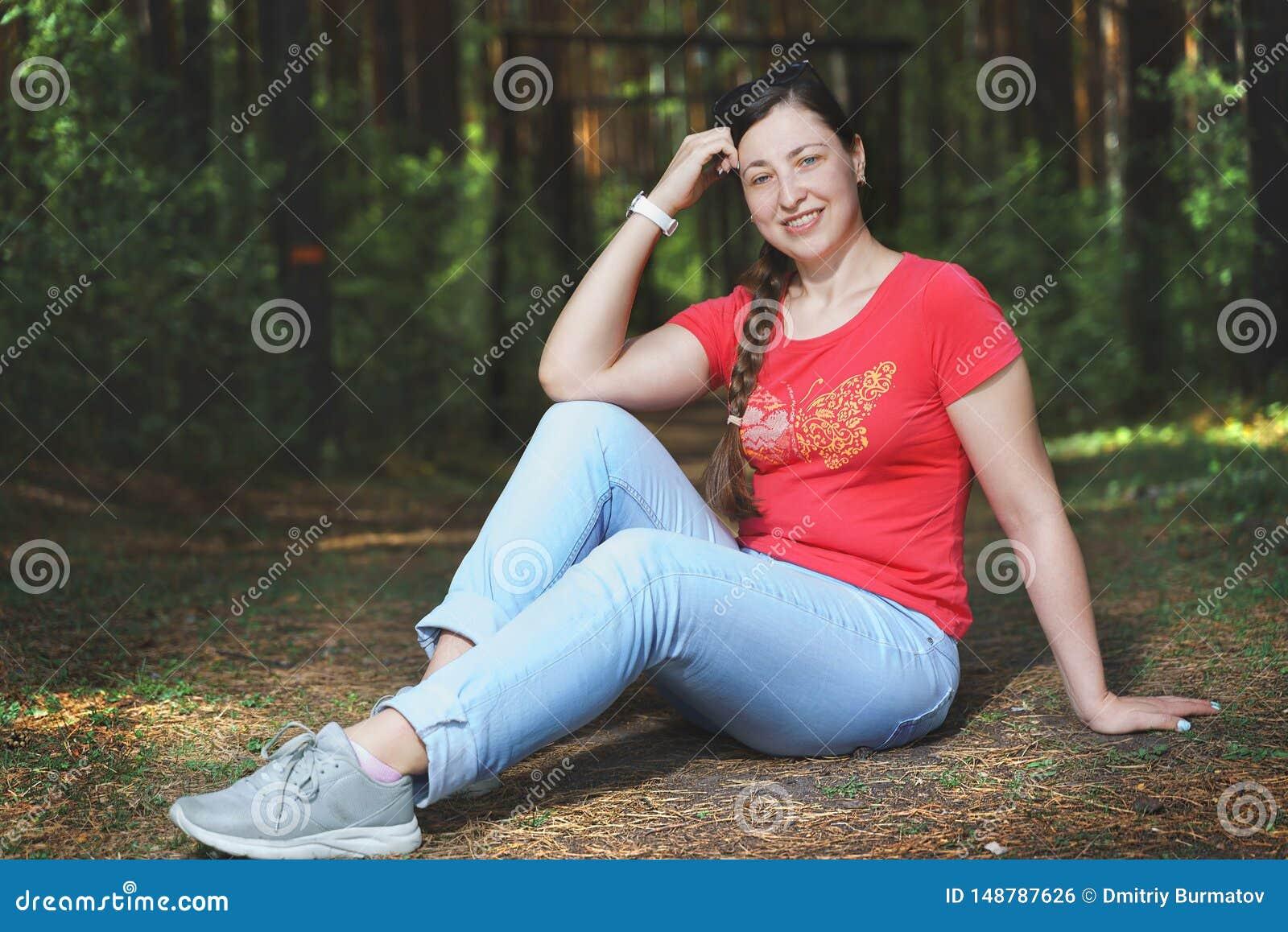 Młody piękny kobiety obsiadanie na podłodze szczęśliwych uczuciu i Jest ubranym przypadkowych ubrania
