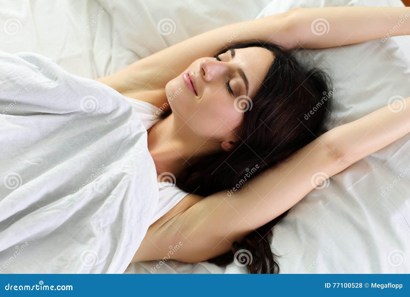 Młody piękny ono uśmiecha się i brunetki kobiety lying on the beach w łóżku
