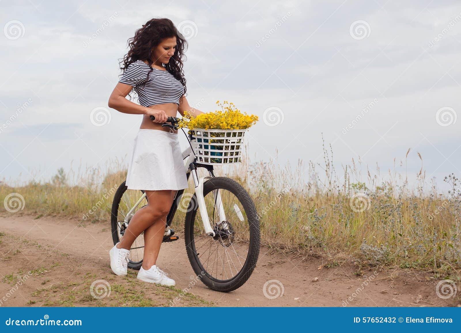 Młody piękny womanon rower w wsi