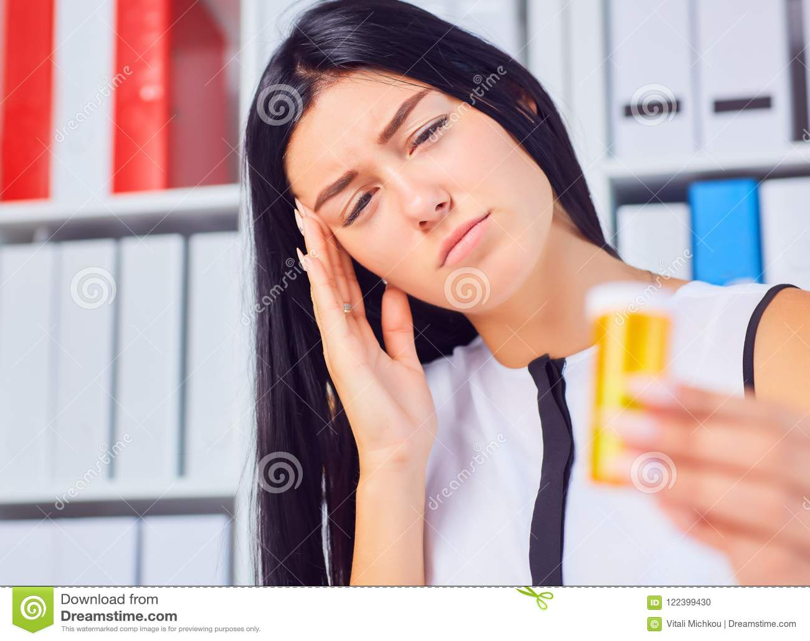 Młody piękny zmęczony chory kobiety obsiadanie w miejscu pracy w biurowej mienie butelce z pigułkami Żeński czuciowy bad przy pra