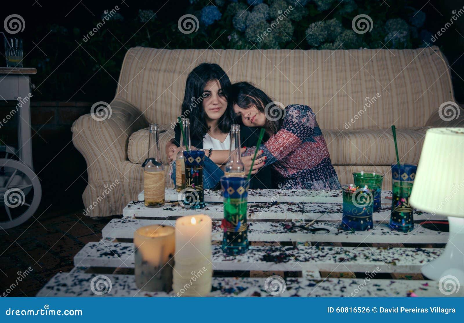 Młody pijący kobiety dosypianie obejmujący przyjaciel