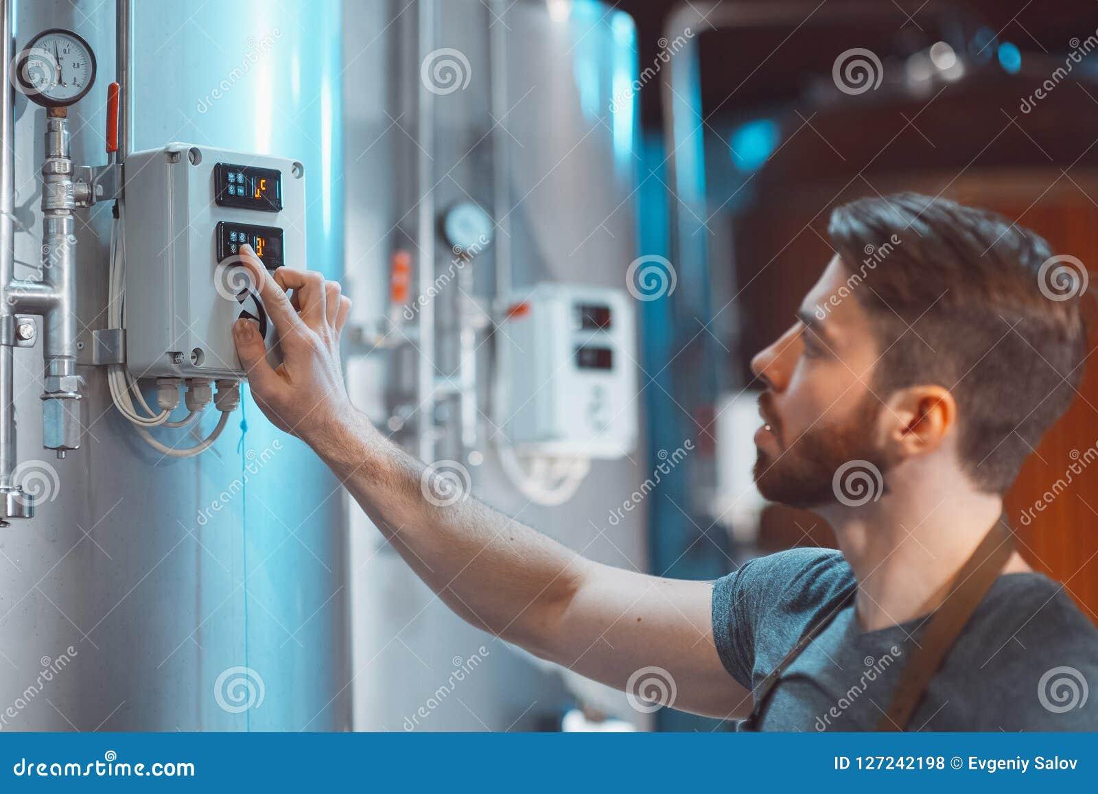 Młody piwowar przystosowywa temperaturowych czujniki na piwnych zbiornikach