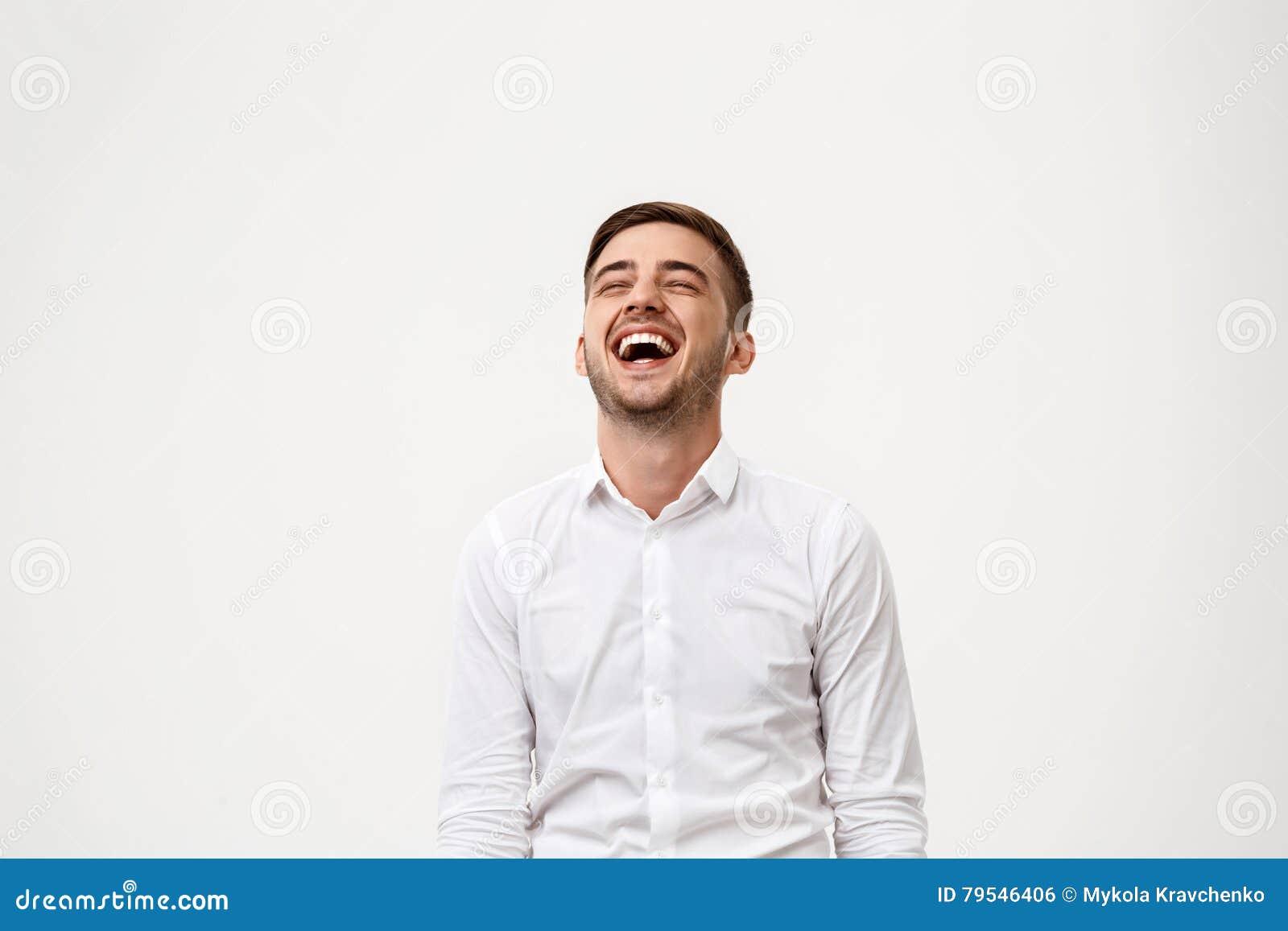 Młody pomyślny biznesmen ono uśmiecha się, śmiający się nad białym tłem