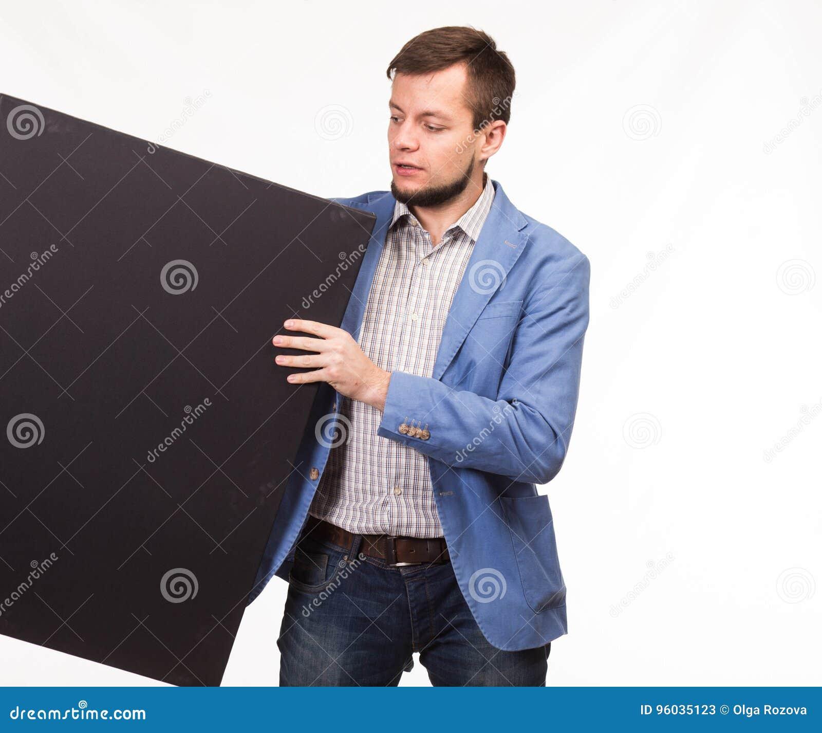 Młody poważny mężczyzna pokazuje prezentację, wskazuje na plakacie