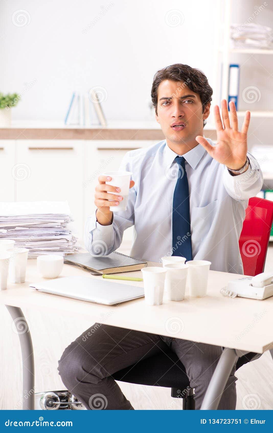 Młody pracownik uzależniający się kawa