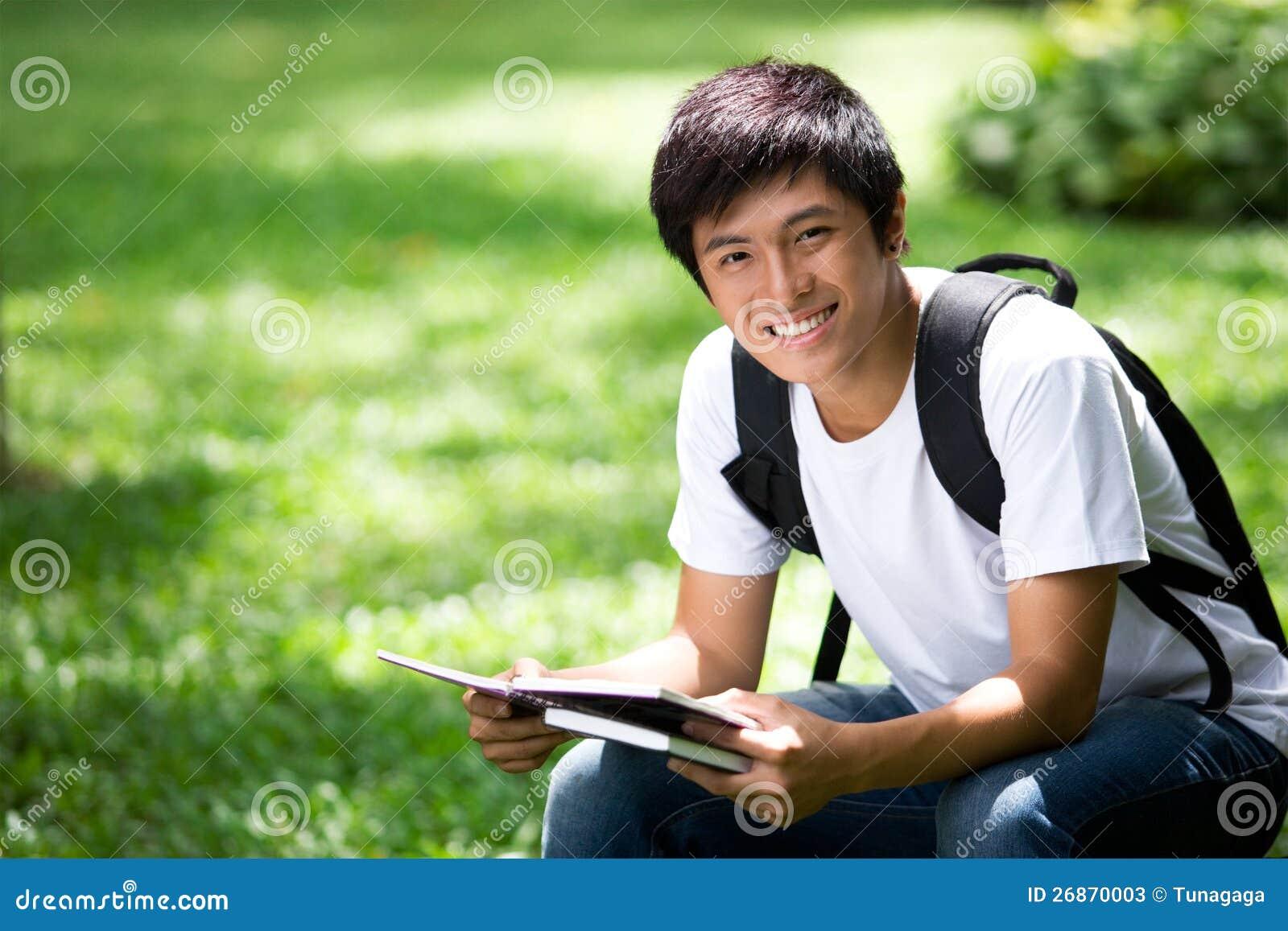 Młody przystojny Azjatycki uczeń z laptopem