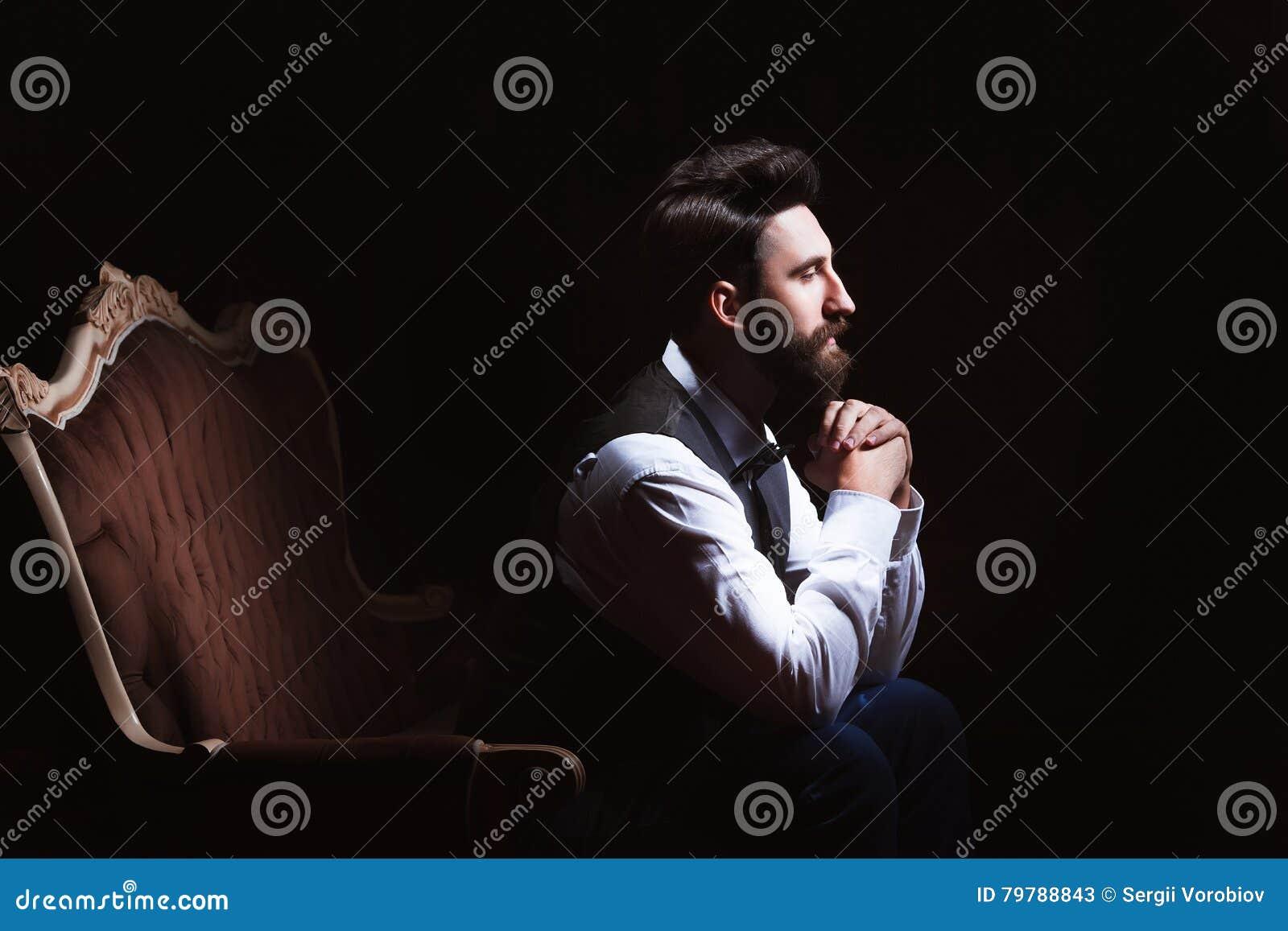 Młody przystojny brodaty caucasian mężczyzna obsiadanie na rocznik kanapie Perfect fryzura i skóra Być ubranym kamizelkę, biała k