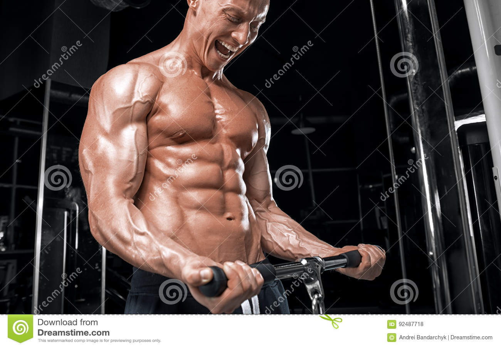 Młody przystojny facet robi ćwiczeniom w gym