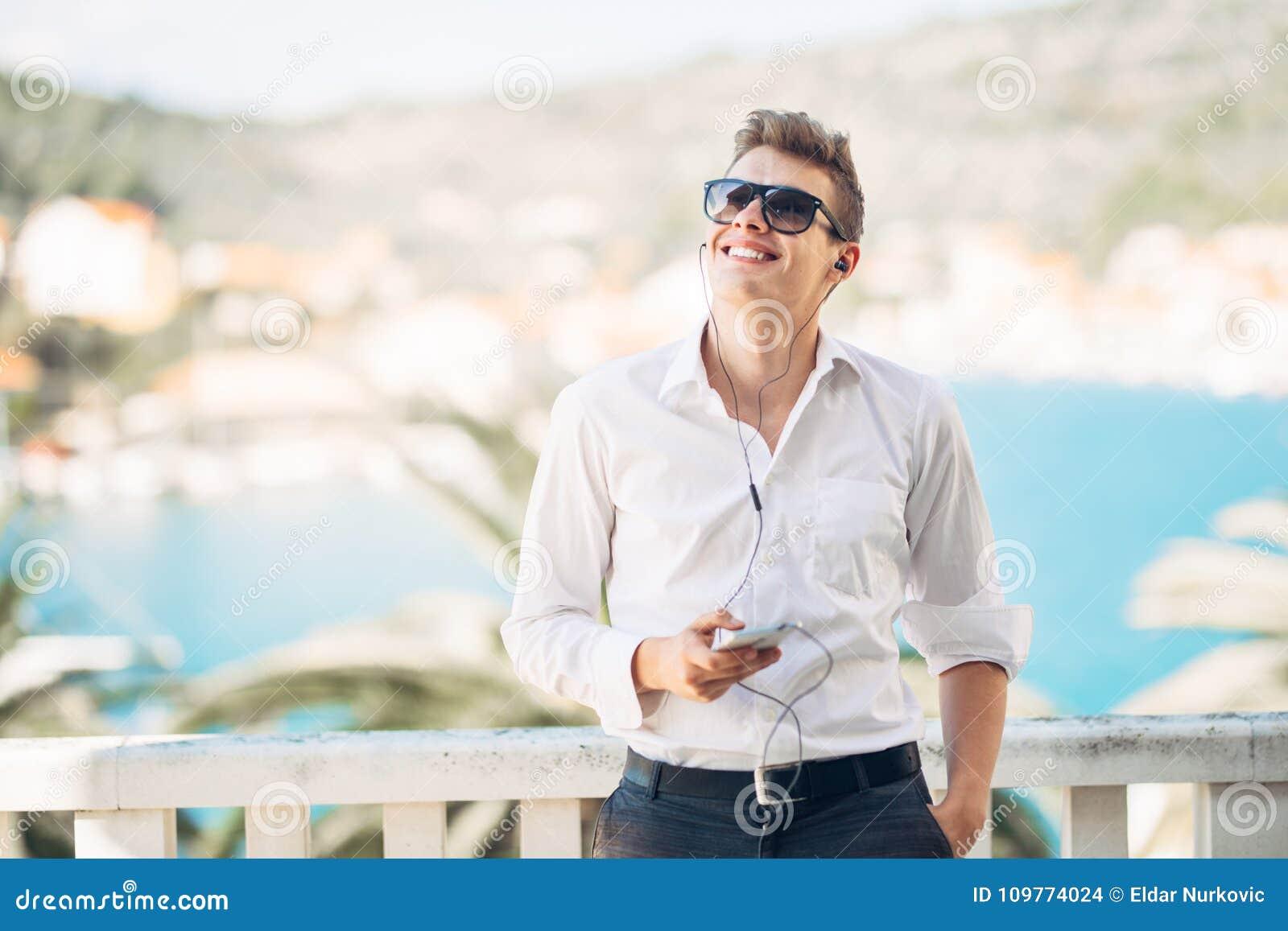 Młody przystojny mężczyzna cieszy się pobyt przy luksusowym hotel w kurorcie z panoramicznym widokiem na morzu