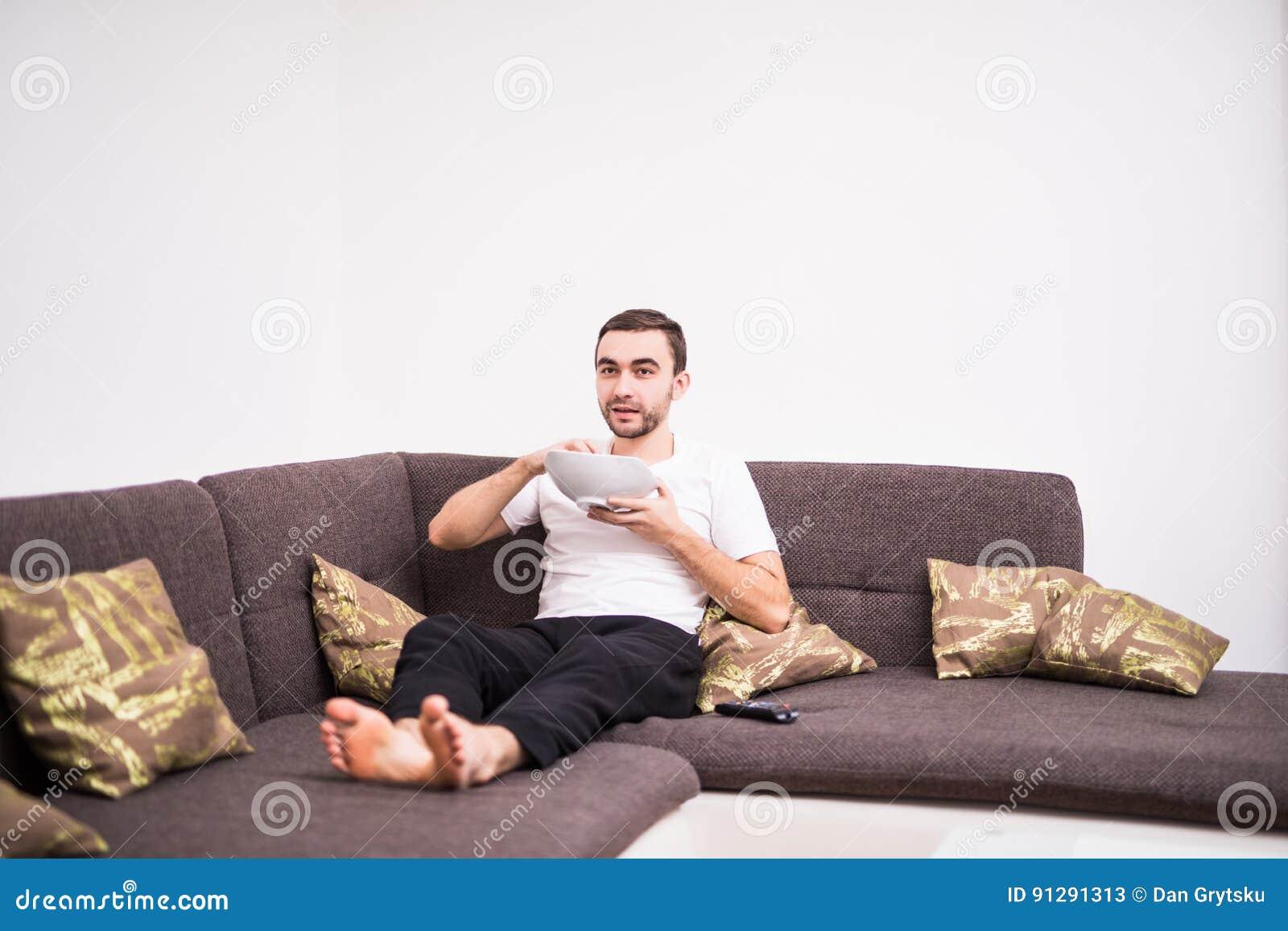 Młody przystojny mężczyzna ogląda TV na kanapie w mieszkaniu w domu