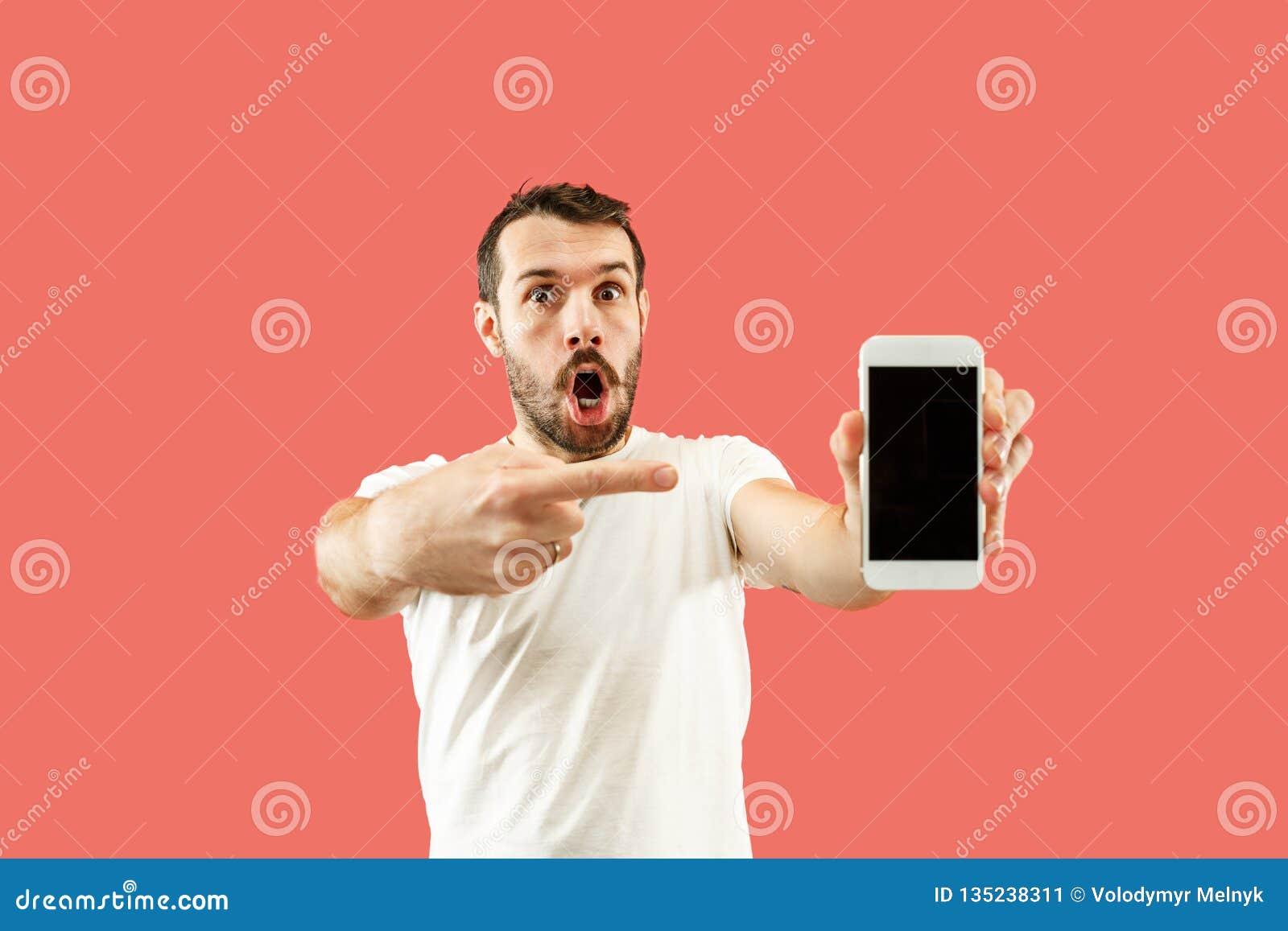 Młody przystojny mężczyzna pokazuje smartphone ekran odizolowywającego na koralowym tle w szoku z niespodzianki twarzą