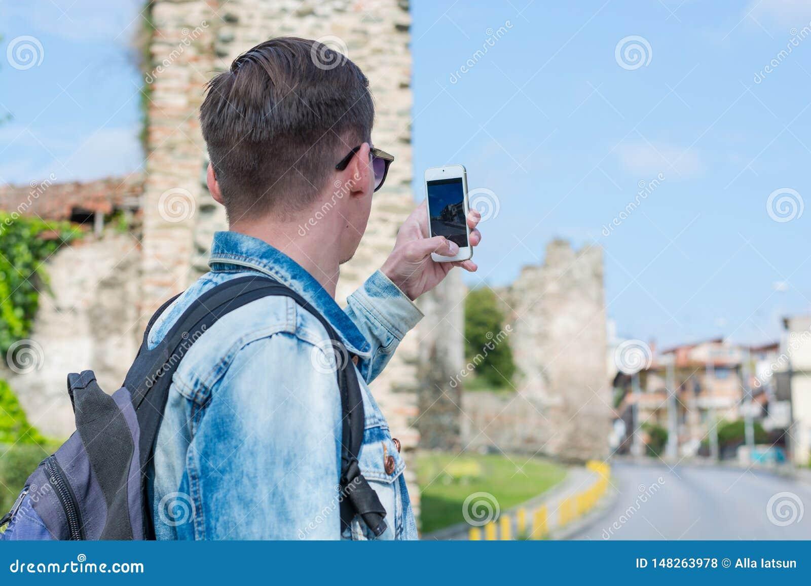 Młody przystojny mężczyzna, turysta, z plecakiem bierze obrazkom na smartphone Trigonion wierza w Saloniki, Grecja