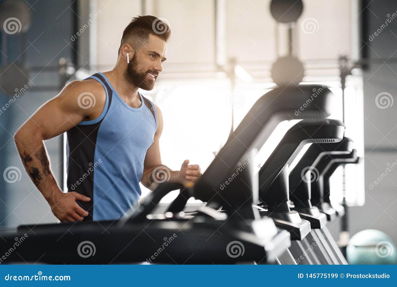 Młody przystojny mężczyzny bieg na karuzeli przy gym