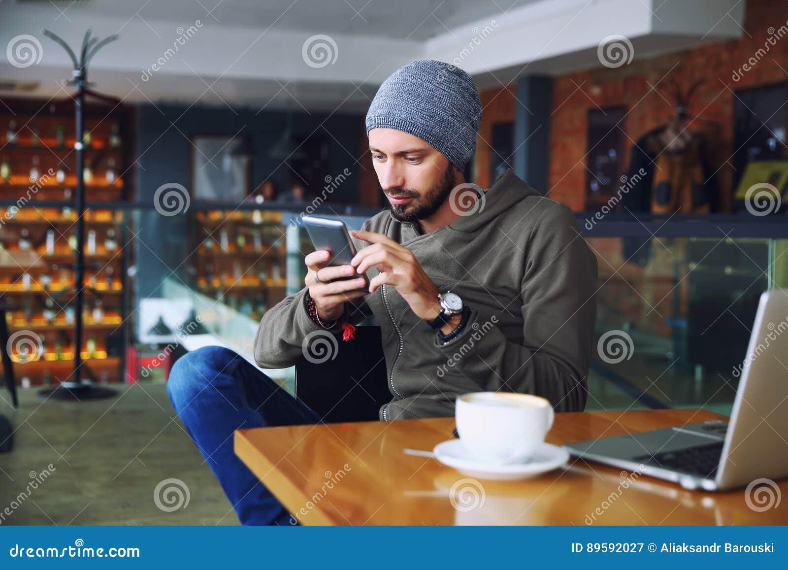 Młody przystojny modnisia mężczyzna z brody obsiadaniem w cukiernianym opowiada telefonie komórkowym, trzymający filiżankę kawy i