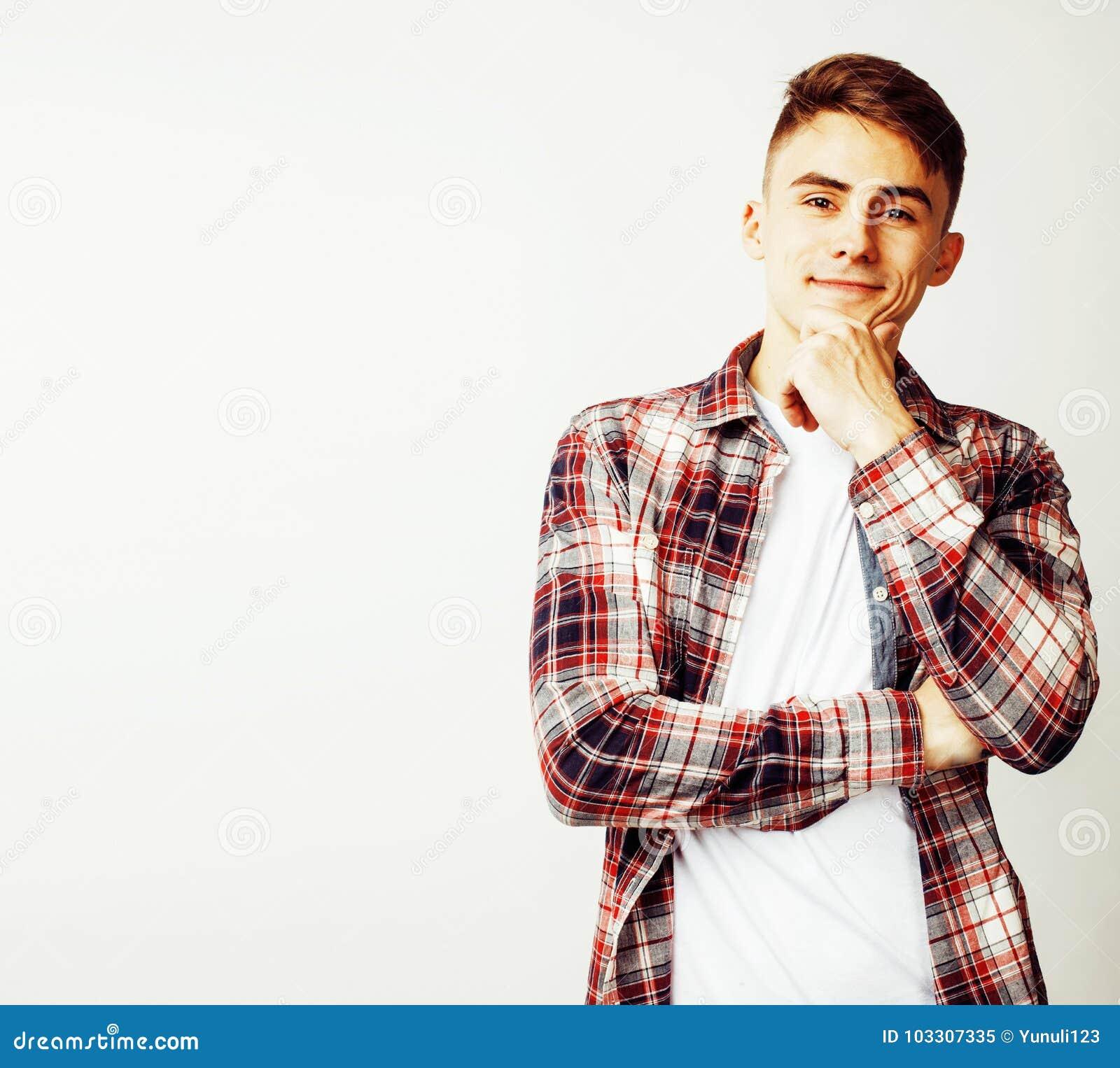 Młody przystojny nastoletni modnisia facet pozuje emocjonalny, szczęśliwy ono uśmiecha się, przeciw białemu tłu, stylów życia lud