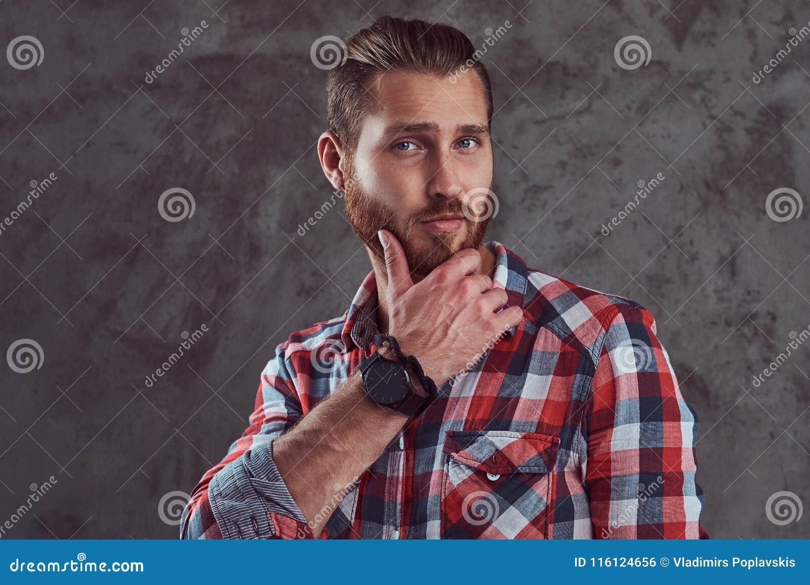 Młody przystojny rudzielec modela mężczyzna w flanelowej koszula na szarym tle
