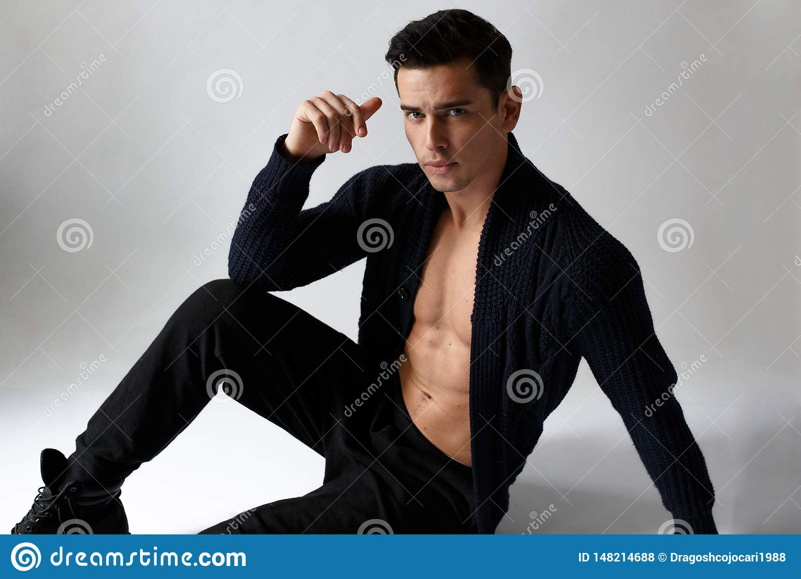 Młody przystojny sportowy mężczyzna pozuje w studiu, jest ubranym w czerni ubraniach, siedzi puszek, na białym tle