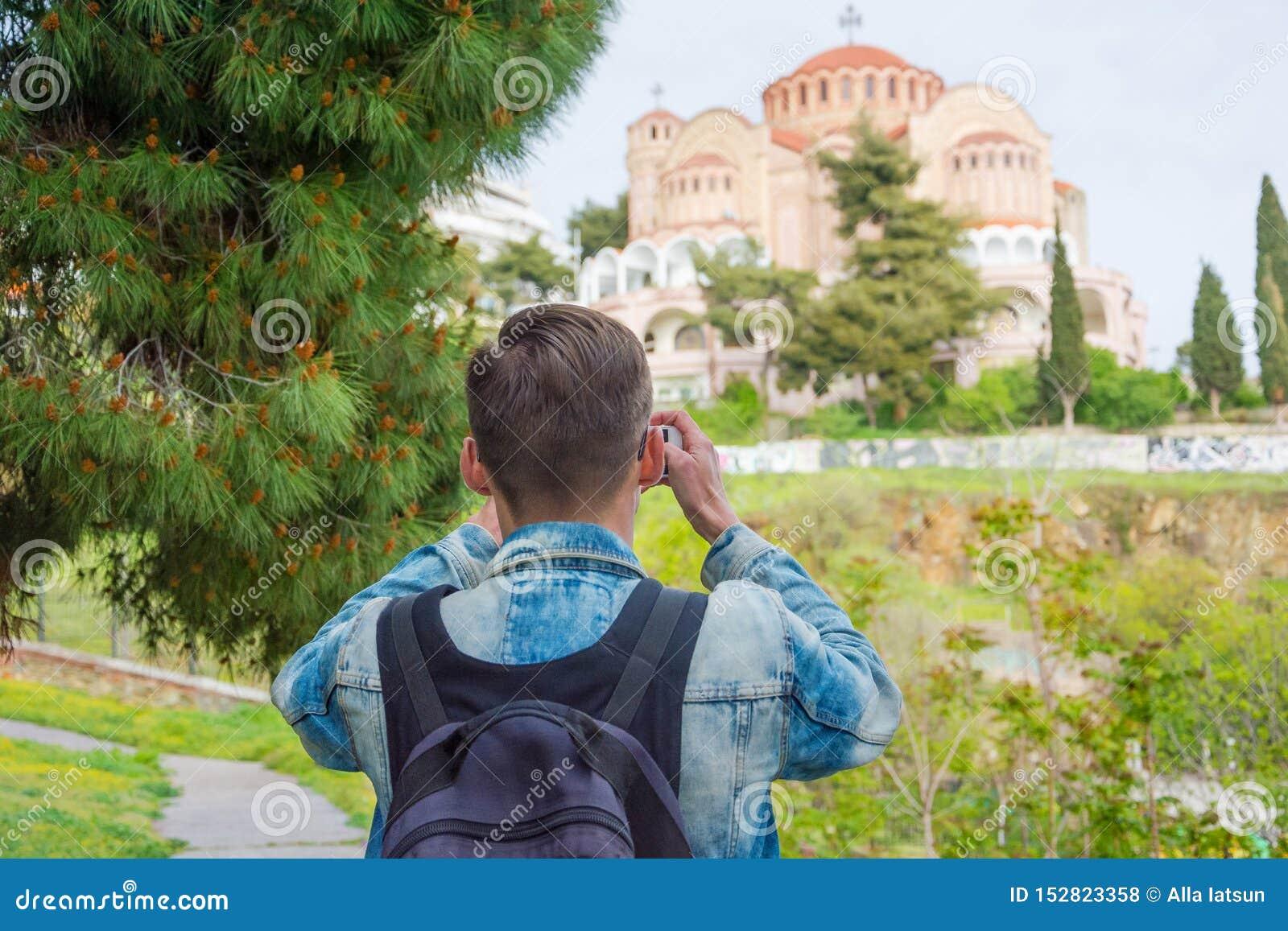 Młody przystojny turysta z plecakiem bierze obrazki na smartphone kościół St Paul w w Ano Poli wewnątrz,