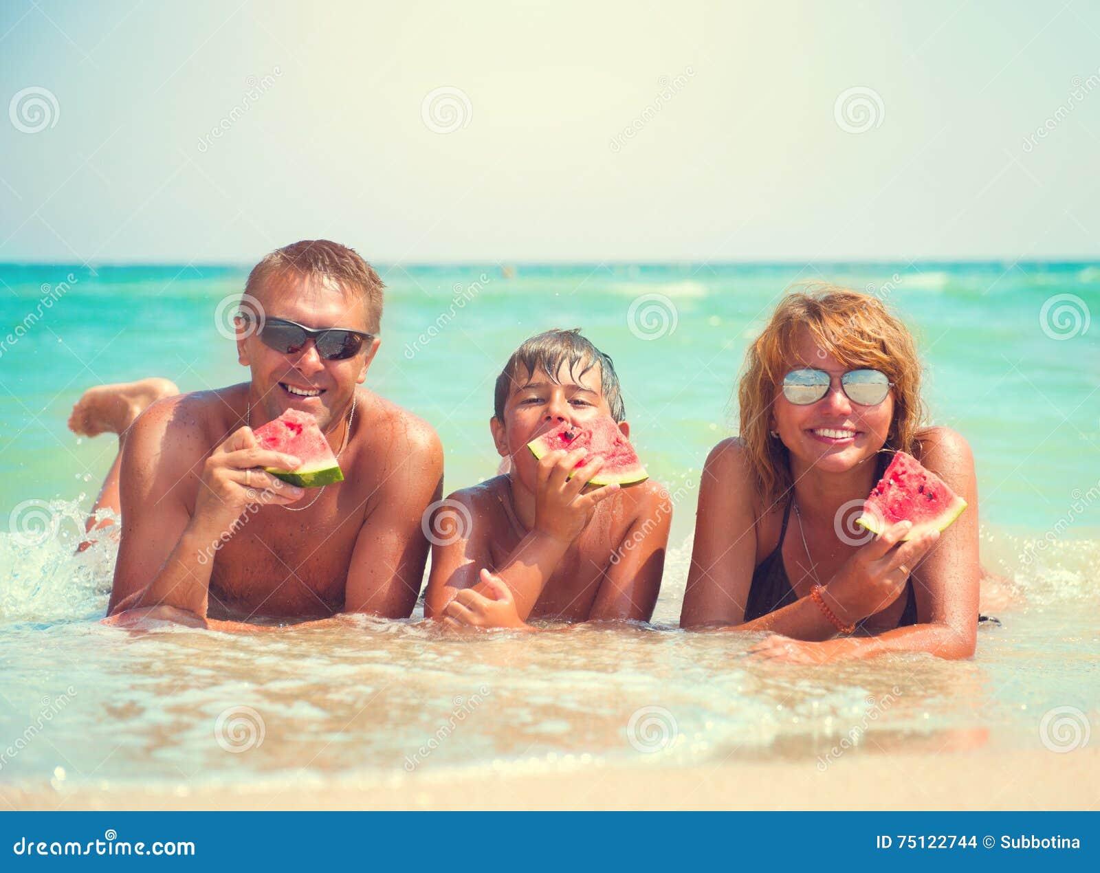Młody rodzinny lying on the beach na łasowanie arbuzie i plaży