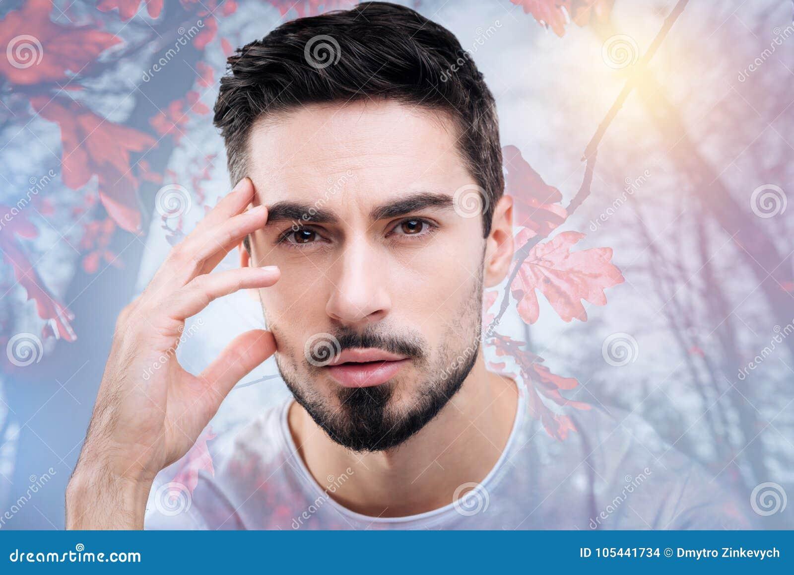 Młody rozważny mężczyzna patrzeje ciekawiący podczas gdy podziwiający piękno natura