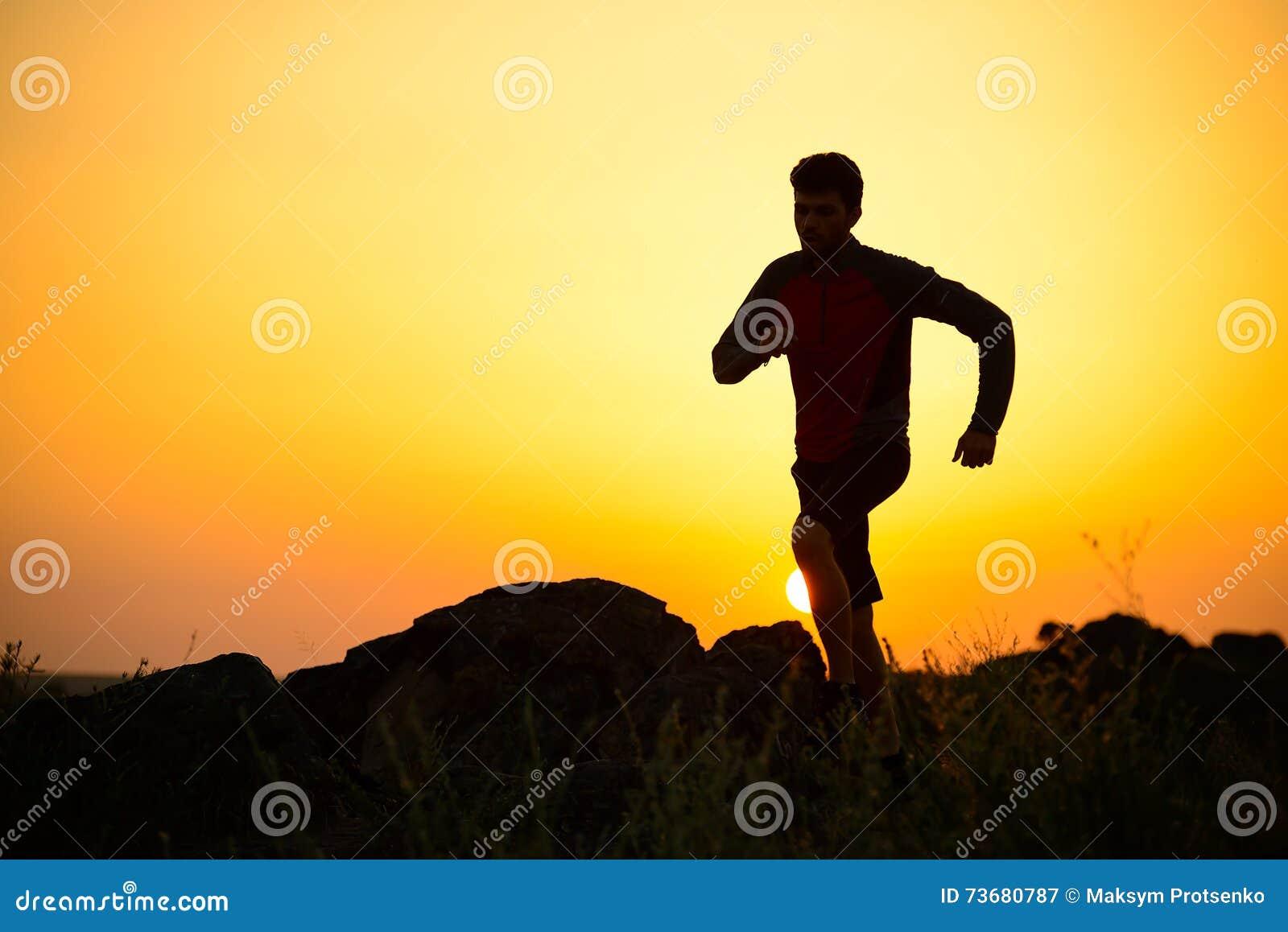 Młody sportowa bieg na Skalistym Halnym śladzie przy zmierzchem aktywny tryb życia