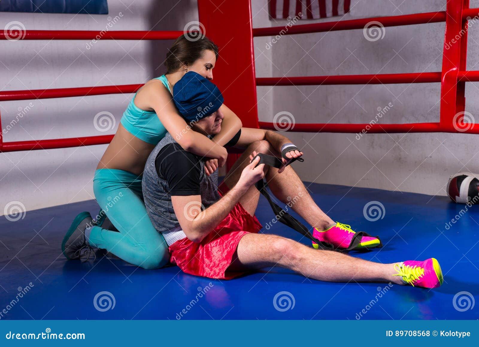 Młody sporty kobiety poparcie i uściśnięcie męski bokser w bokserskim pierścionku