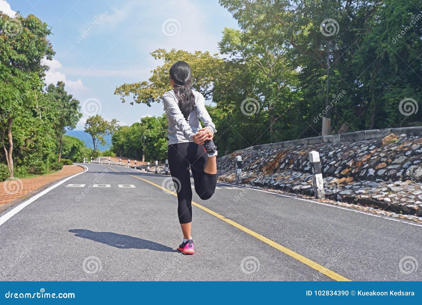Młody sprawności fizycznej kobiety biegacz grże up na drodze przed jogging