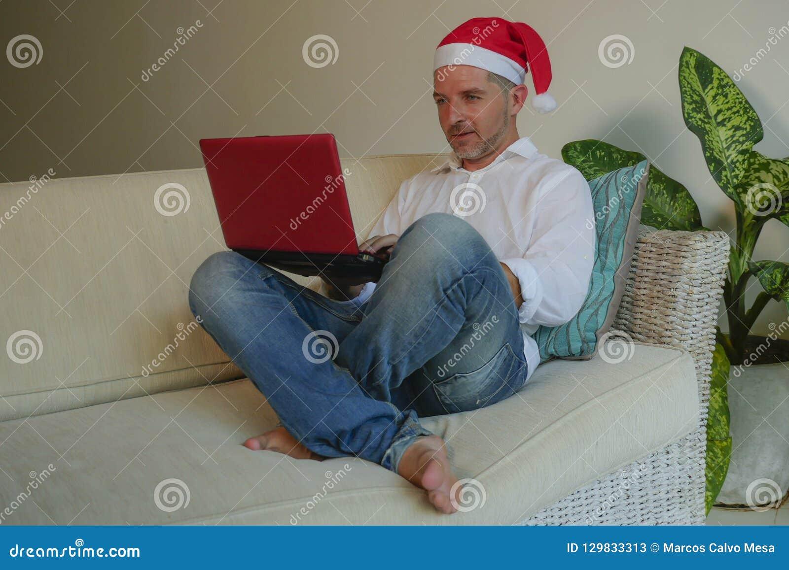 Młody szczęśliwy, atrakcyjny mężczyzna w Santa Klaus kapeluszowej używa karcie kredytowej i laptop dla online Bożenarodzeniowe te