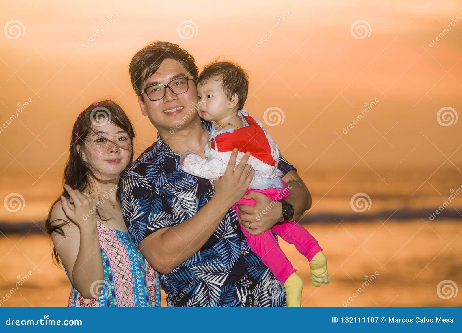 Młody szczęśliwy i piękny Azjatycki Chiński pary mienia dziewczynki córki odprowadzenie na zmierzchu plażowym cieszący się wpólni