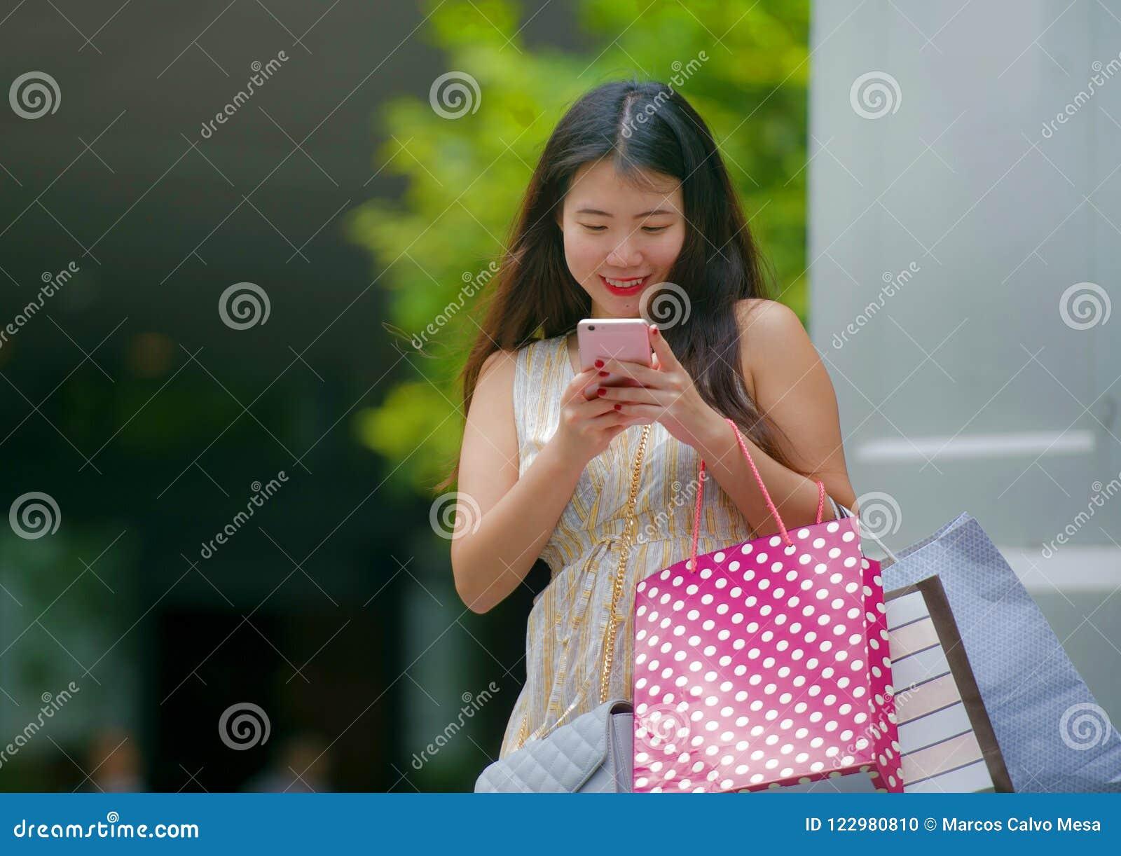 Młody szczęśliwy i piękny Azjatycki Koreański kobiety odprowadzenie na ulicznych przewożeń torba na zakupy używać telefon komórko
