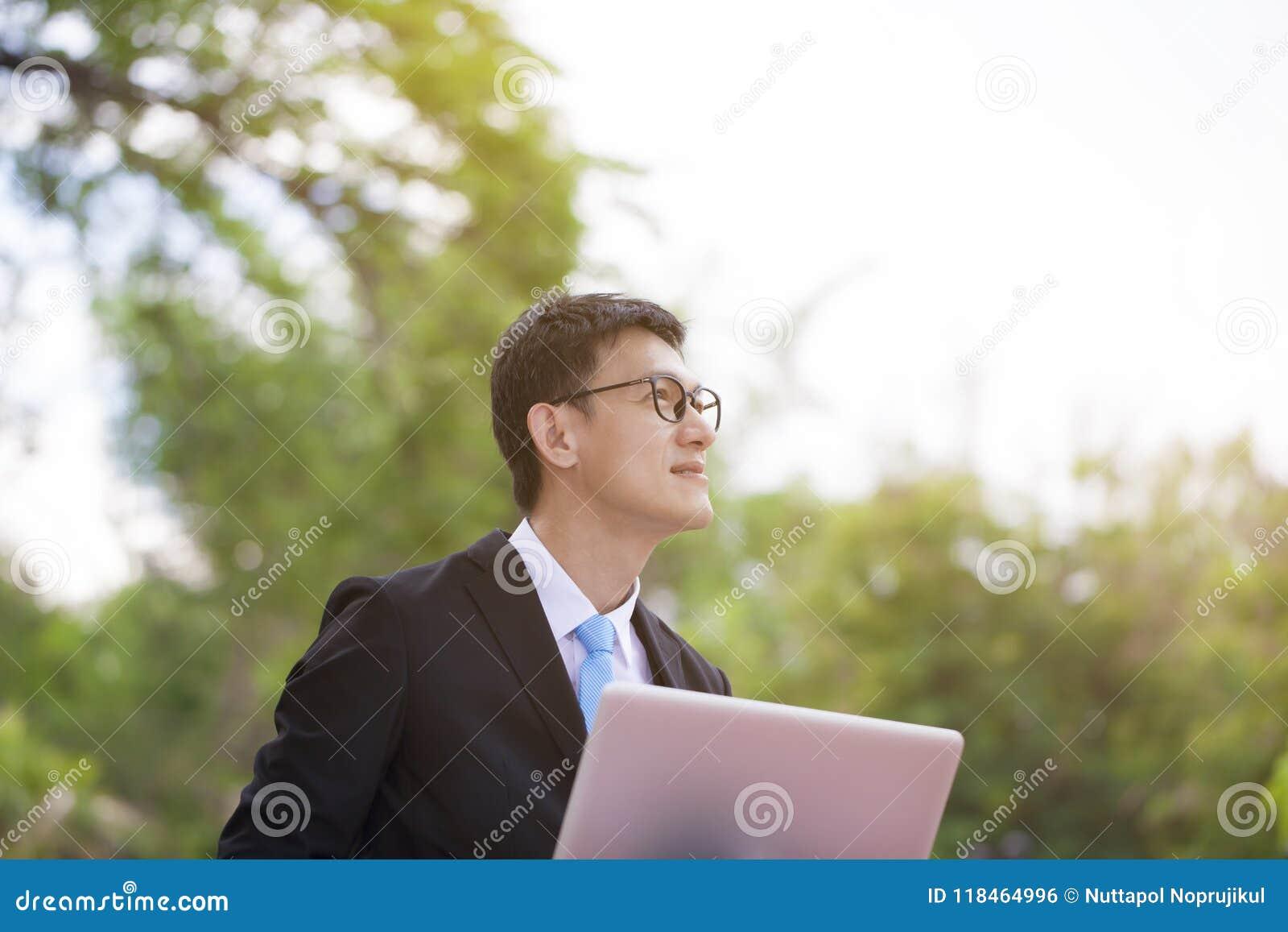 Młody szczęśliwy i pomyślny biznesmen ono uśmiecha się podczas jego br i
