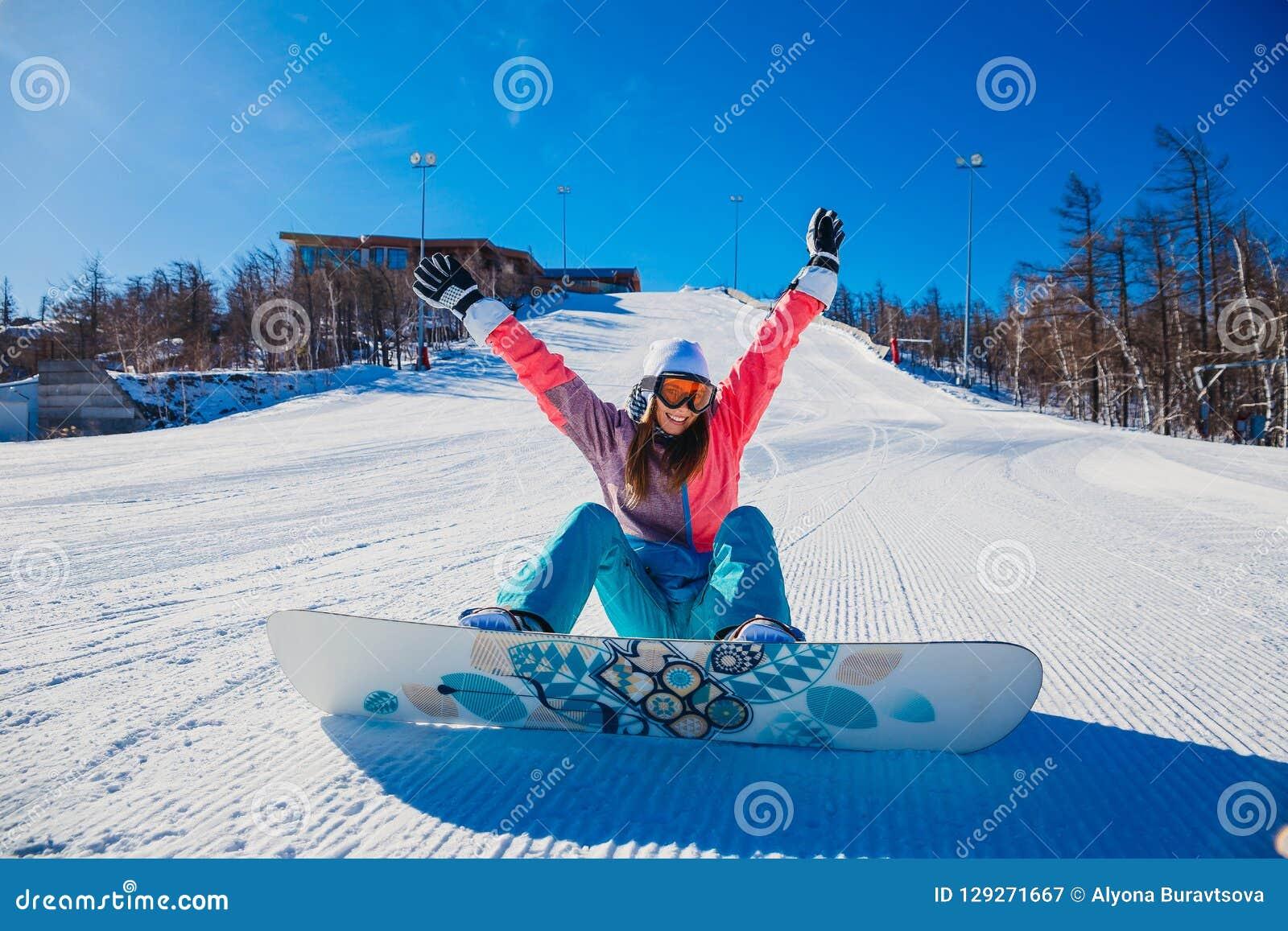 Młody szczęśliwy kobiety snowboarder siedzi dalej na śnieżnym halnym skłonie