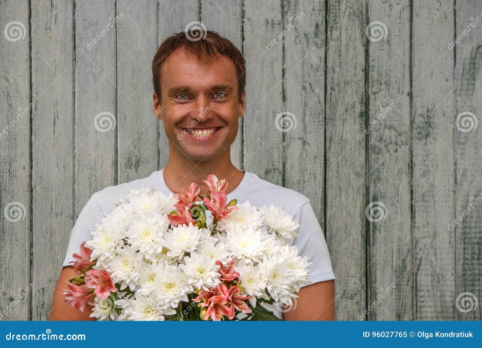 Młody szczęśliwy mężczyzna z białymi kwiatami na drewnianym tle
