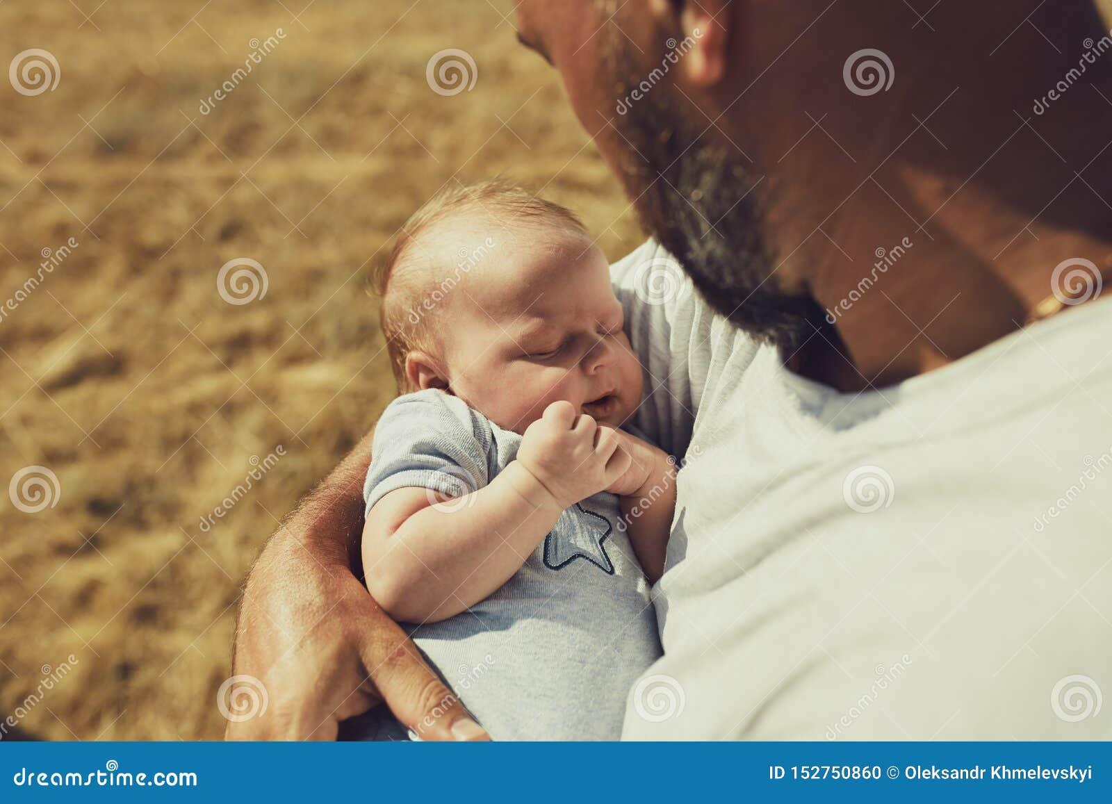 Młody tata trzyma nowonarodzonego dziecka podczas gdy chodzący w naturze szczęśliwy ojciec jest ubranym skróty i koszulkę Mi?dzyn