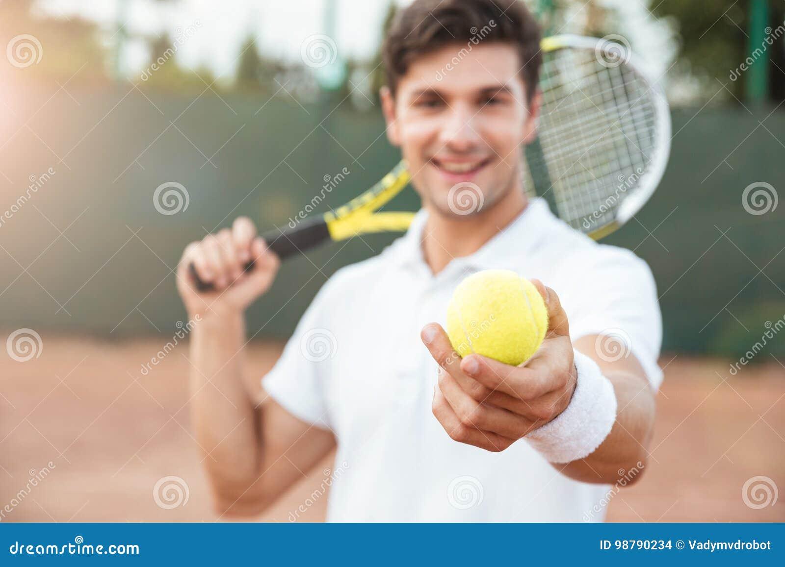 Młody tenisowy mężczyzna daje piłce