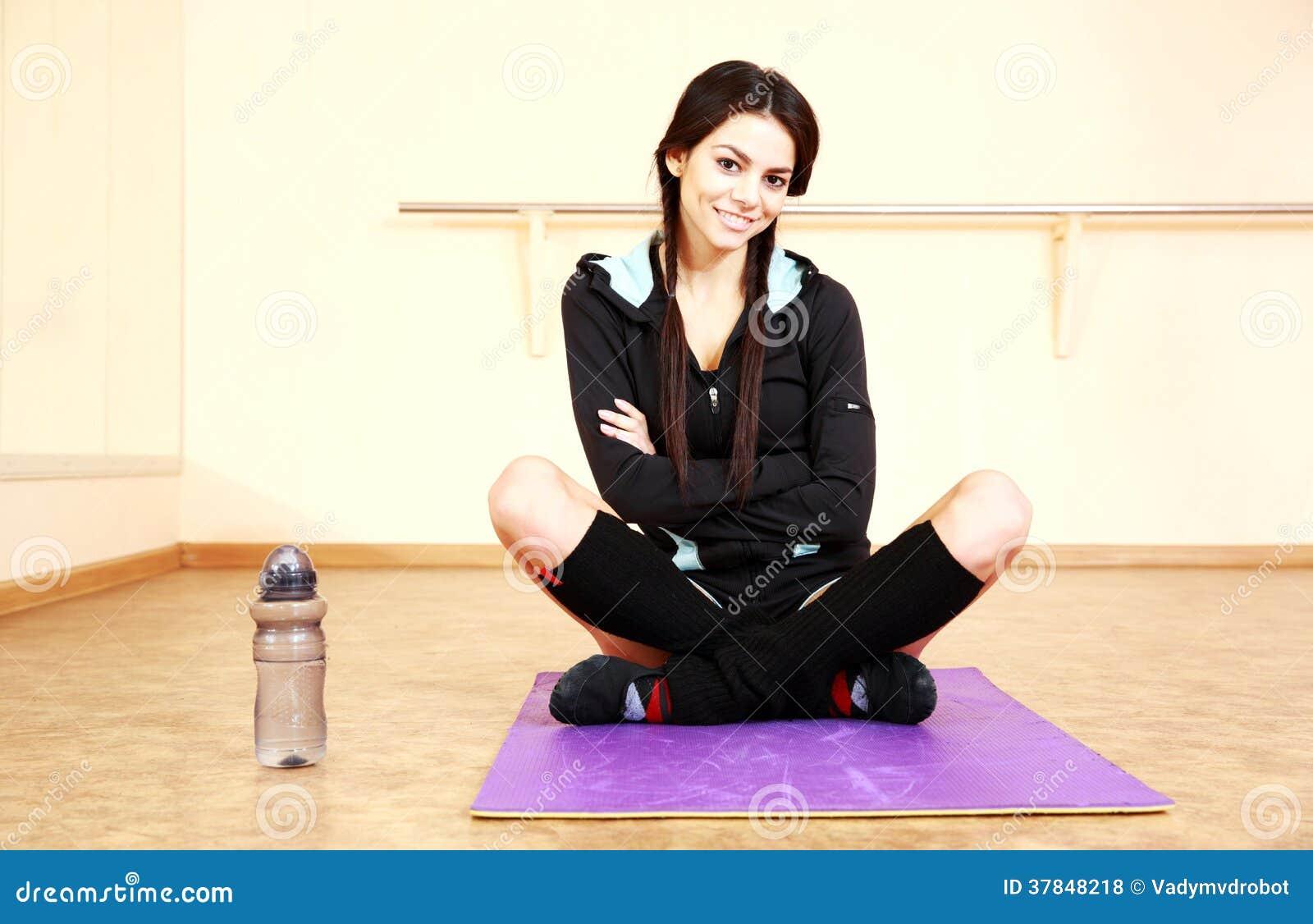 Młody uśmiechnięty dysponowany kobiety obsiadanie na joga macie