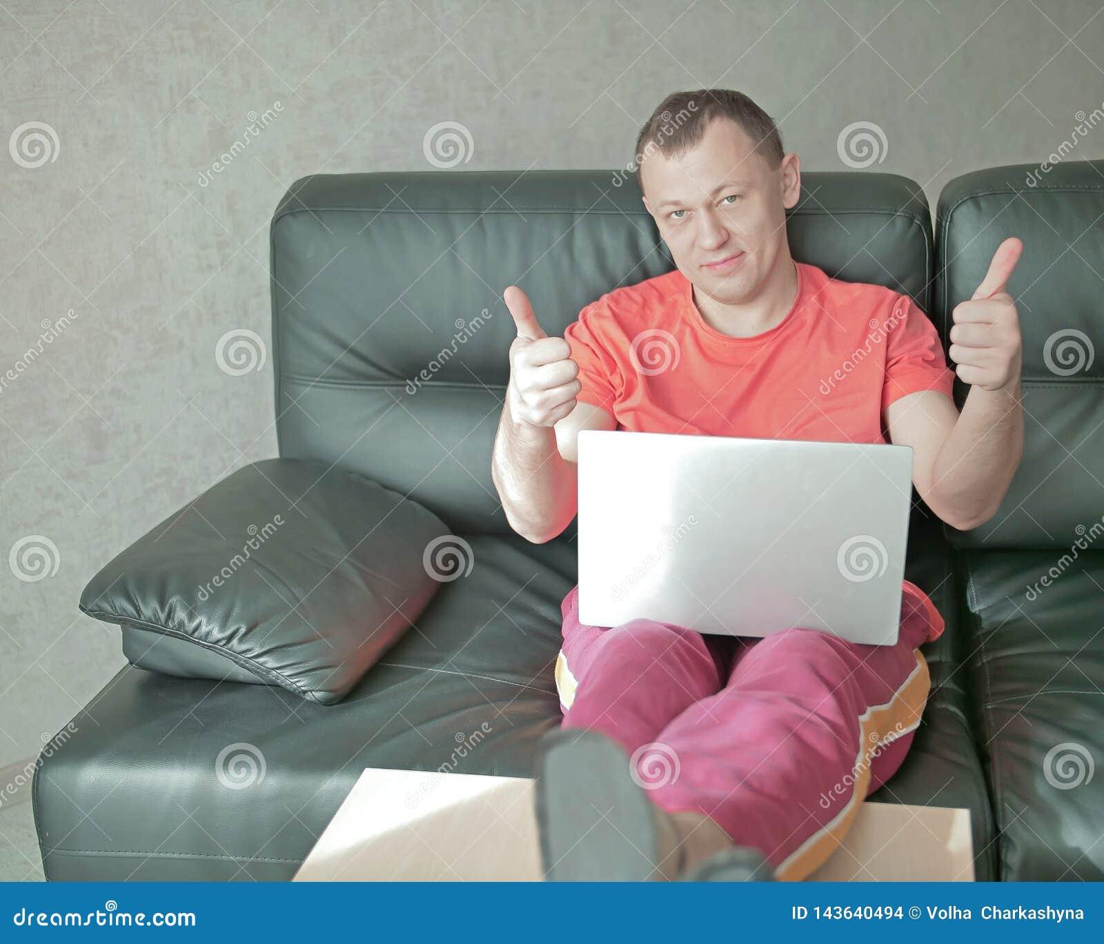 Młody uśmiechnięty mężczyzna z laptopem siedzi na kanapie w domu i trzyma aprobaty, spojrzenia w kamerę