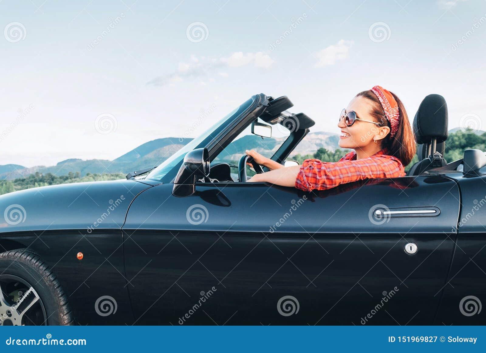 Młody uśmiechnięty rozochocony żeński napędowy retro stylowy odwracalny samochód przy słonecznego dnia czasem