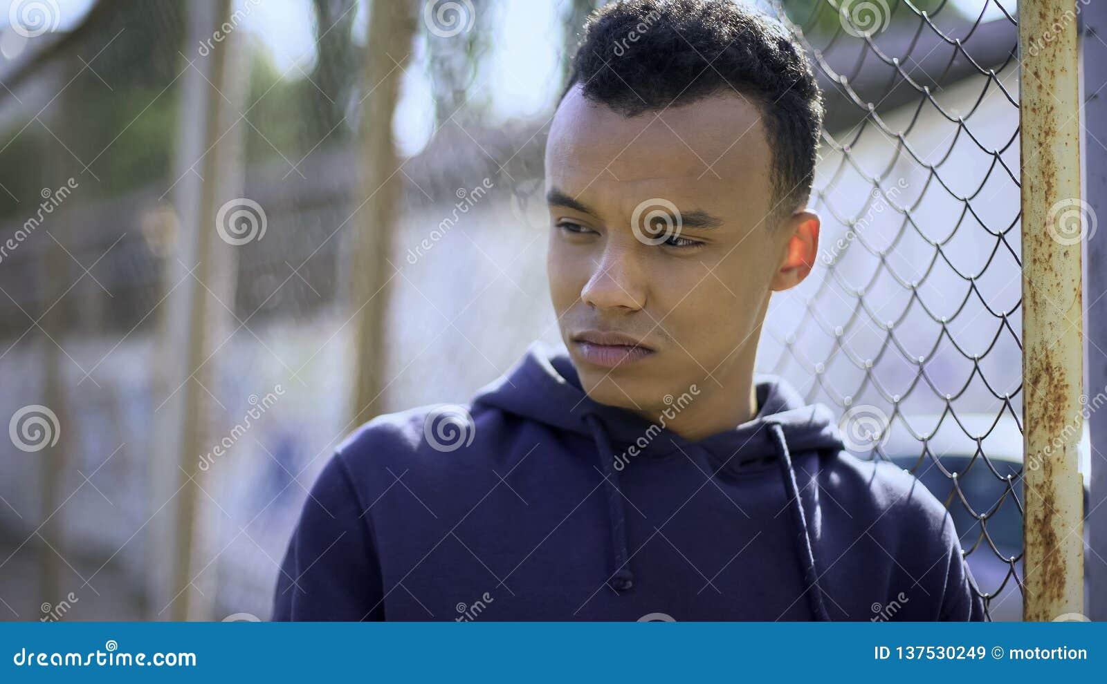 Młody uchodźca od zaburzeniowy rodzinny opierać na ogrodzeniu, osierocony nastolatek