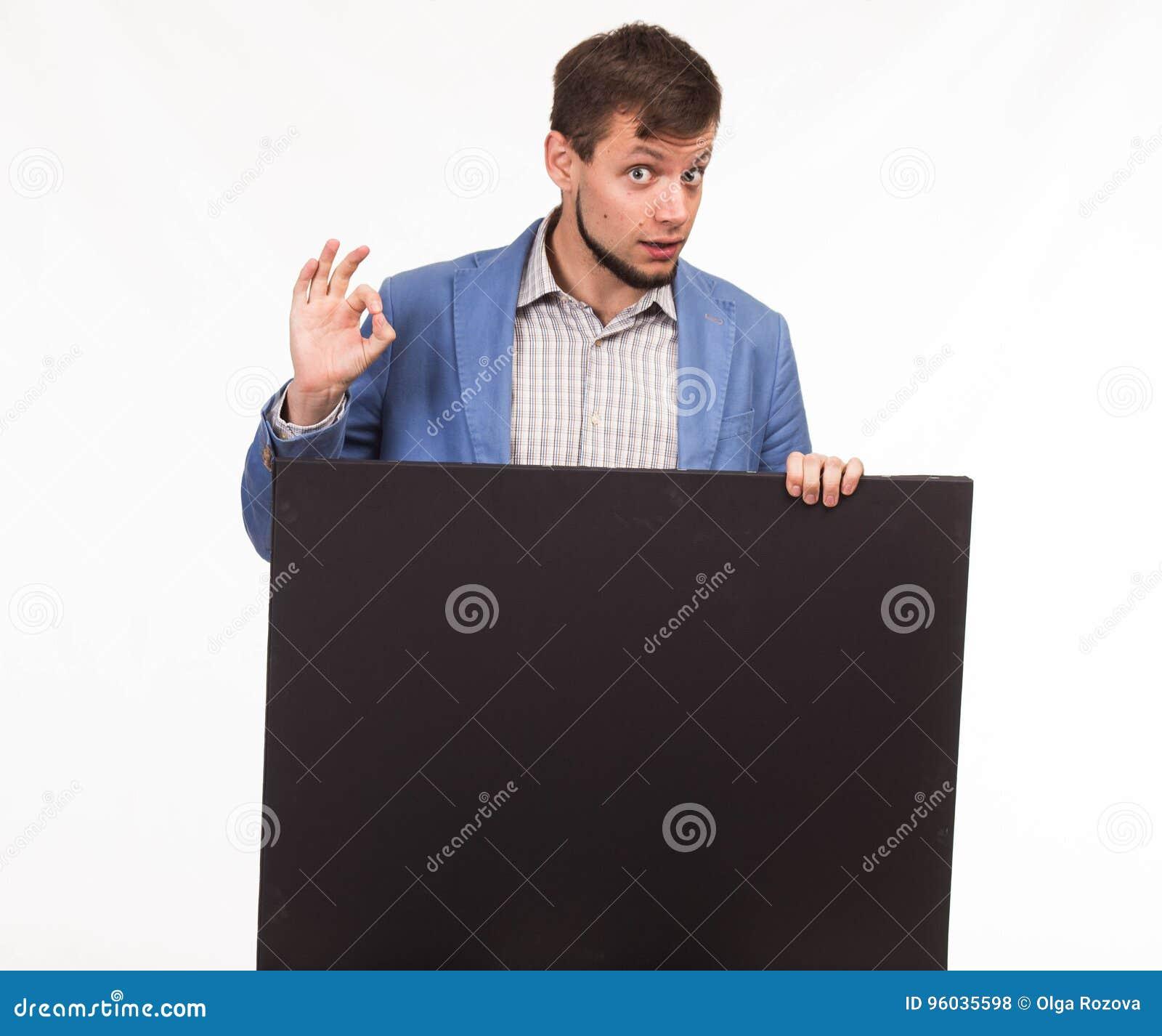 Młody ufny mężczyzna pokazuje prezentację, wskazuje na plakacie