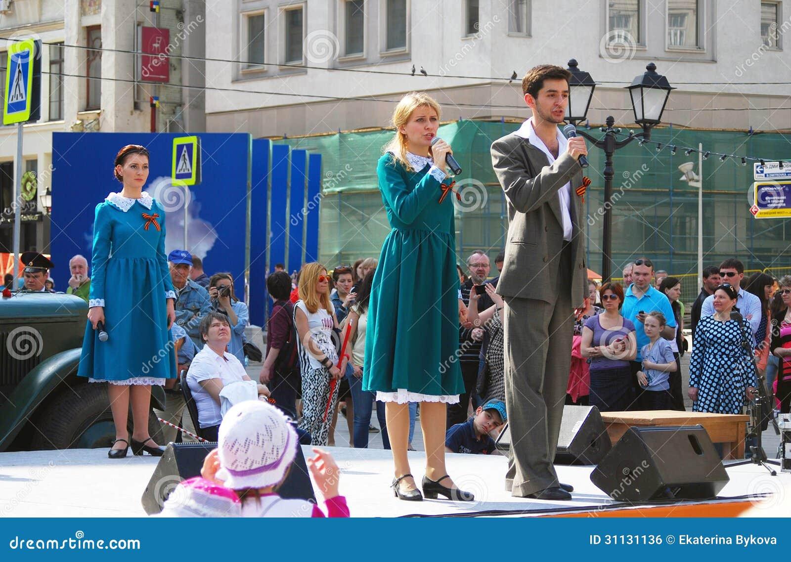 Młodzi aktorzy śpiewają piosenki na scenie