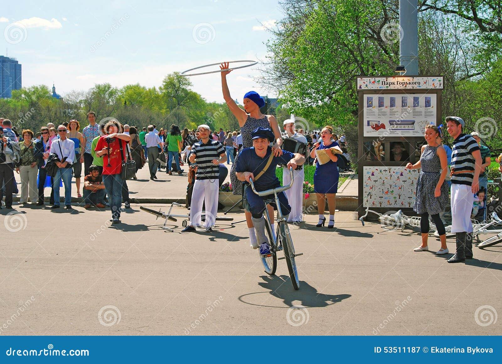 Młodzi aktorzy wykonuje w Gorky parku Wwoman i mężczyzna jedziemy bicykl