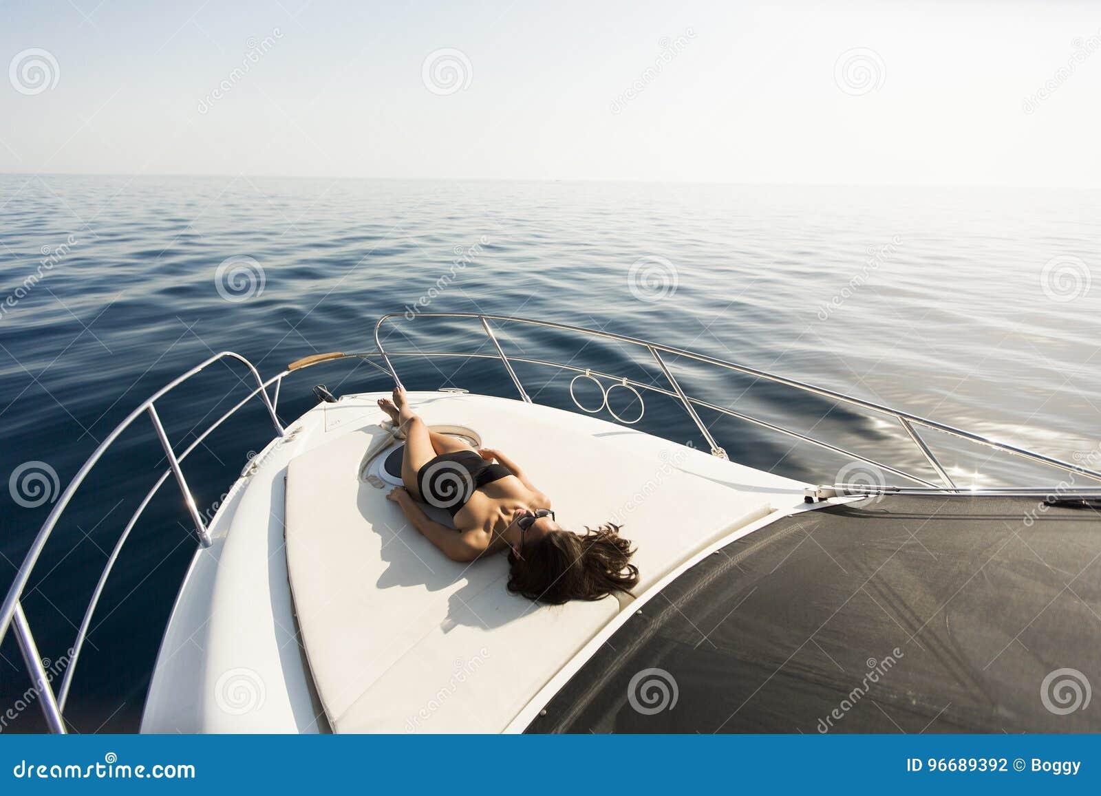 Młodzi atrakcyjni kobiet kłamstwa i sunbathing na łęku luksusowy jacht