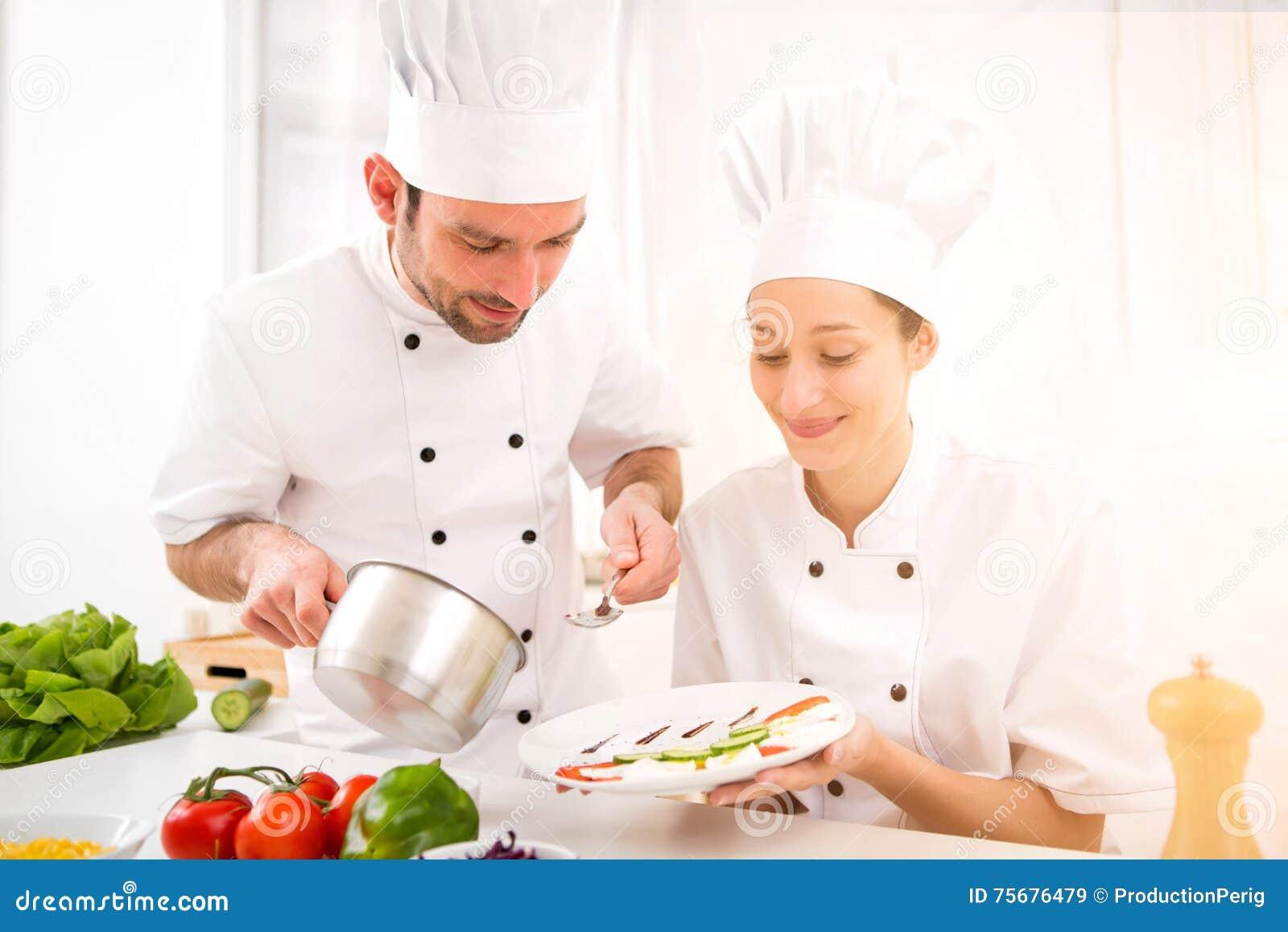 Młodzi attractives profesjonalistów szefowie kuchni gotuje wpólnie