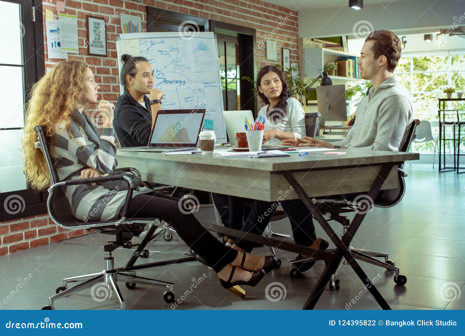 Młodzi biznesmeni caucasian i azjatykci spotykają drużyny