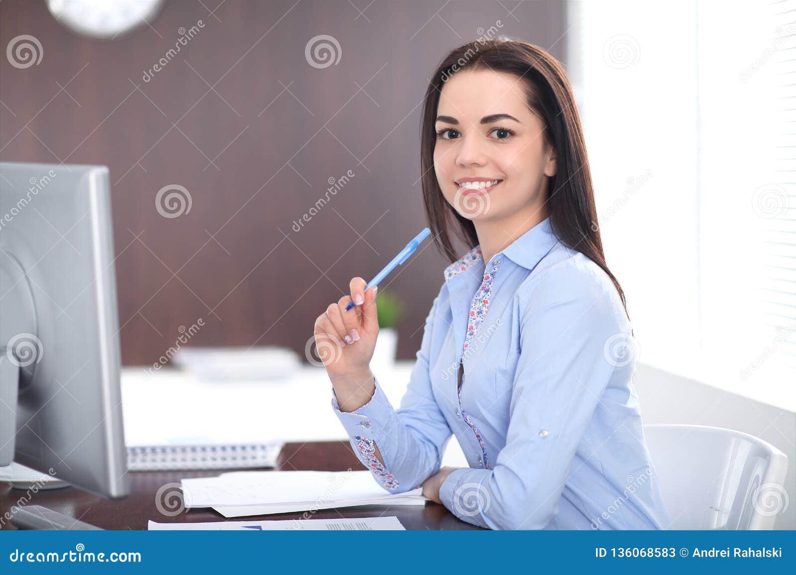 Młodzi brunetki biznesowej kobiety spojrzenia jak studencka dziewczyna pracuje w biurze Latynoska lub latyno-amerykański dziewczy