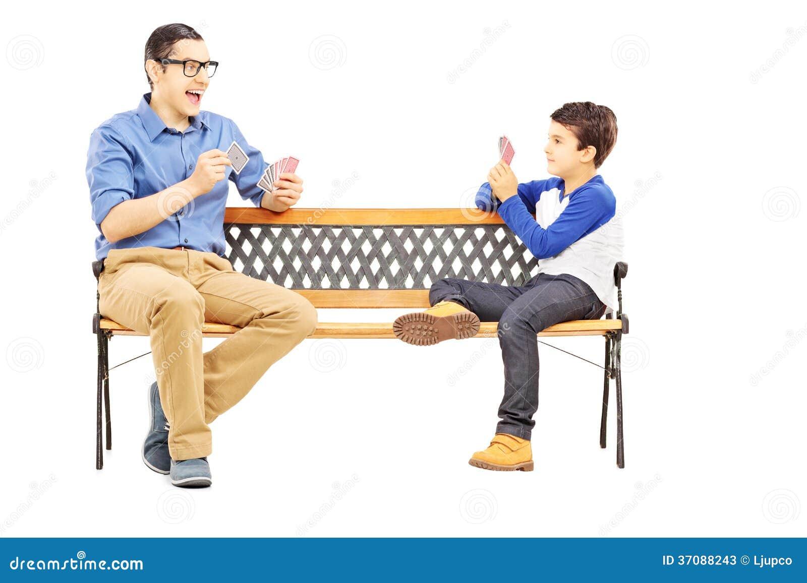 Download Młodzi Chłopiec Karta Do Gry Z Jego Starym Kuzynem Sadzającym Na ławce Obraz Stock - Obraz złożonej z dziecko, joyce: 37088243