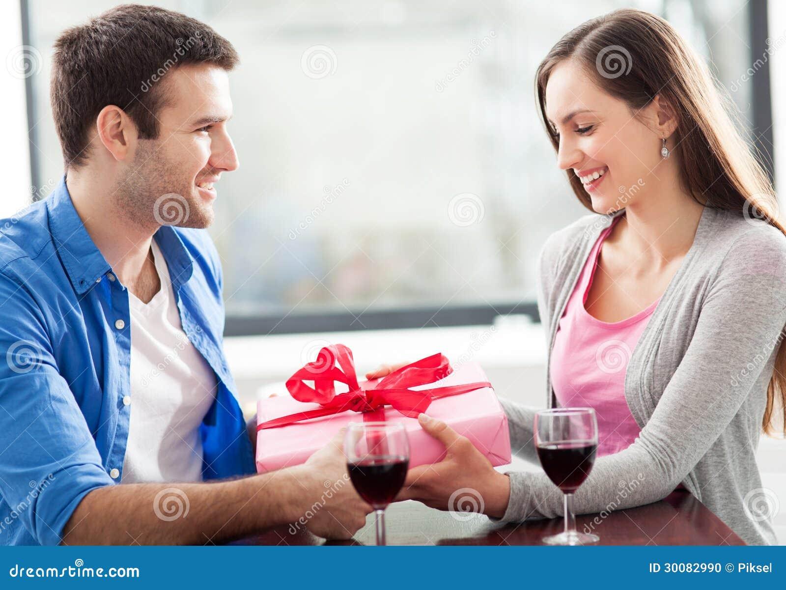 Mężczyzna daje kobieta prezentowi przy kawiarnią
