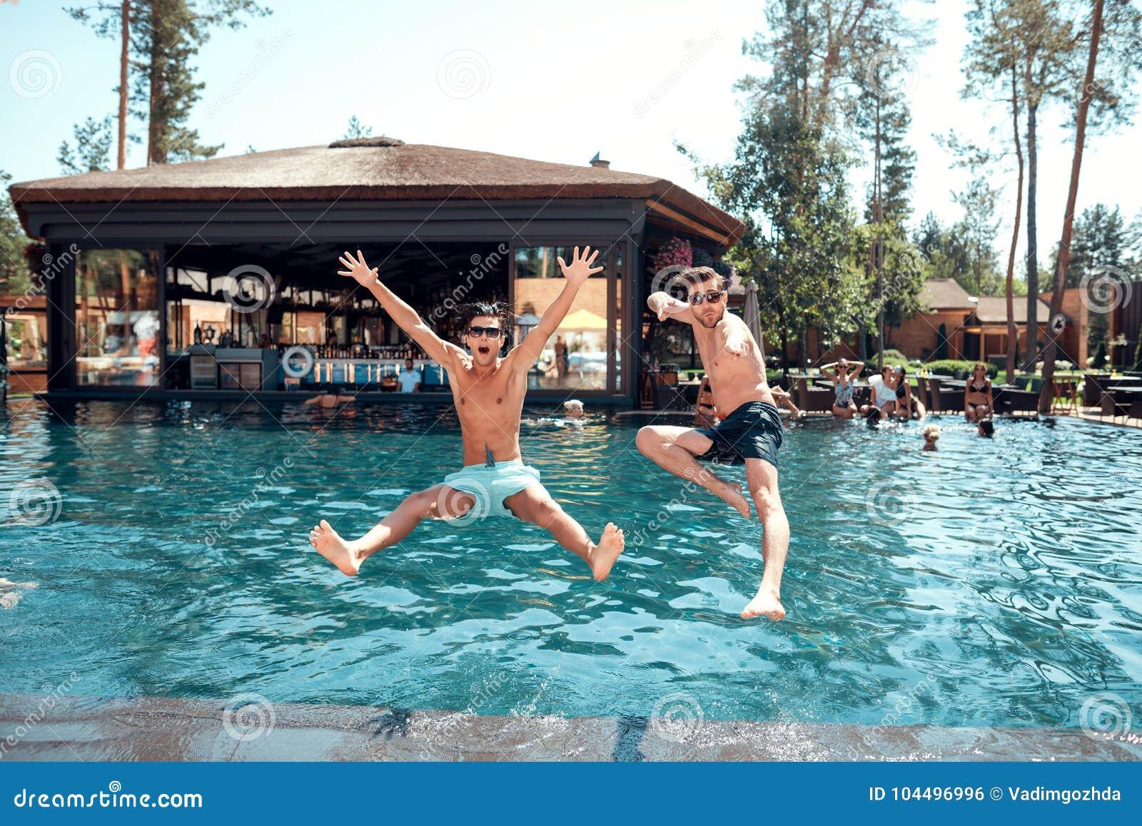 Młodzi faceci i dziewczyny skaczą w basen