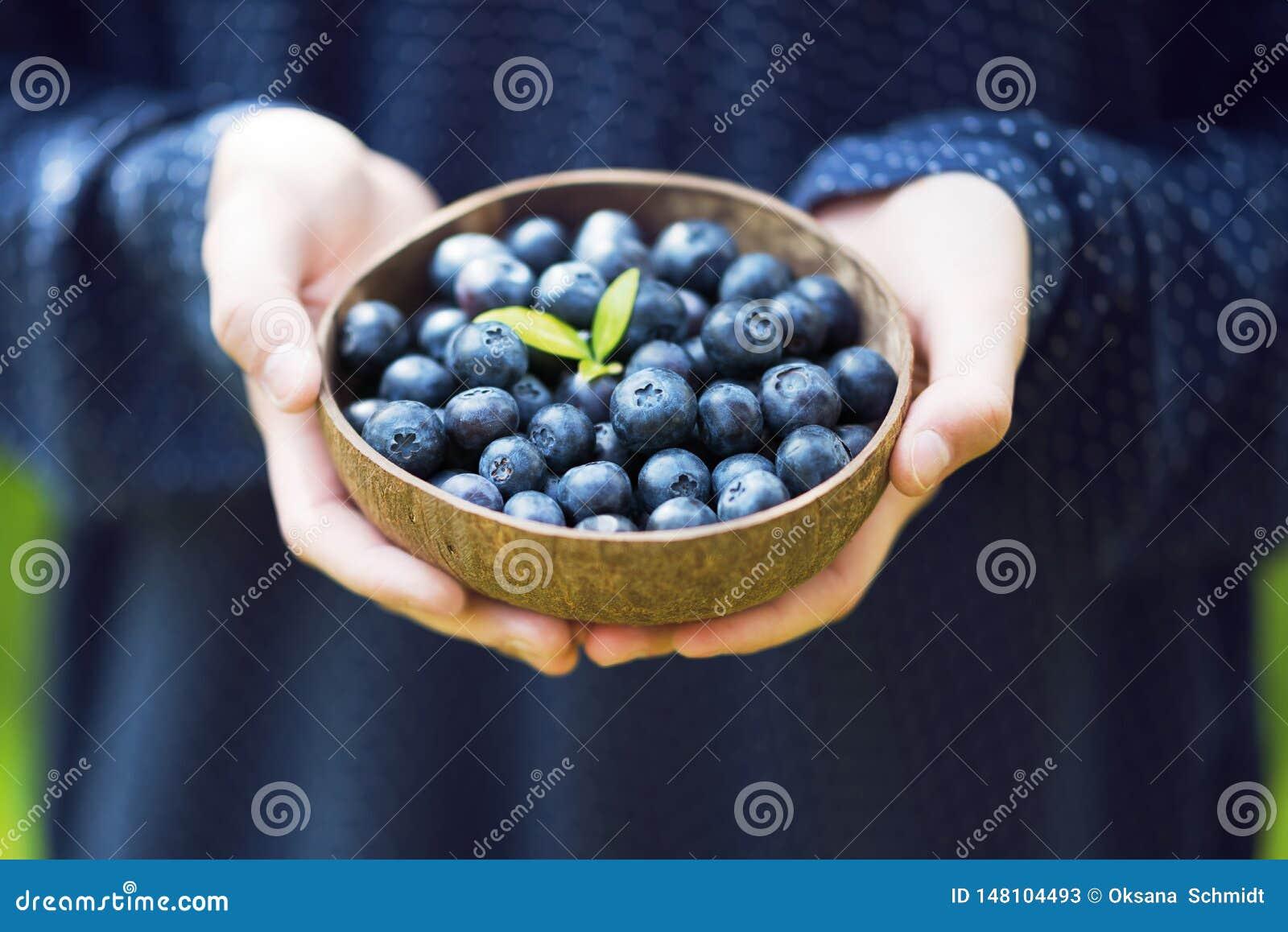 Młodzi girl's wręczają trzymać puchar z świeżymi dojrzałymi czarnymi jagodami